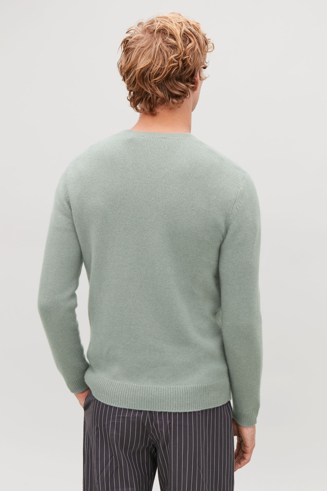 Model side image of Cos cashmere jumper with rectangle stitches in green