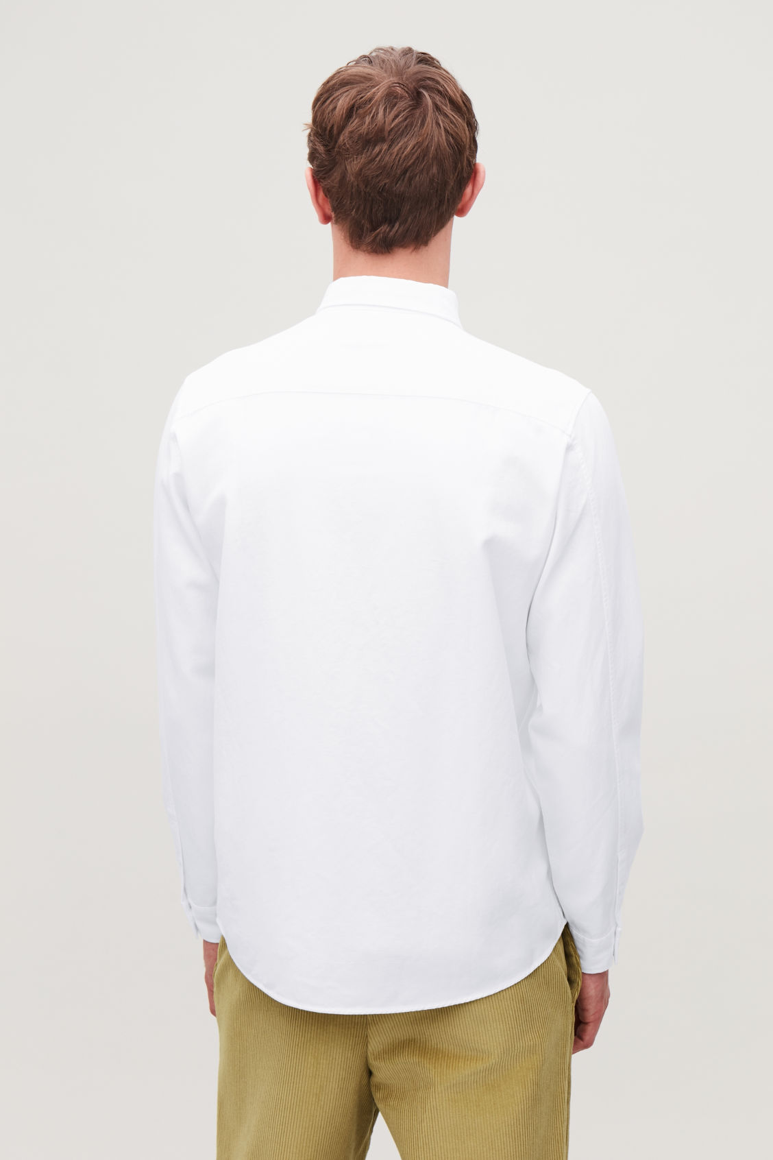 Model side image of Cos cotton button-down shirt  in white