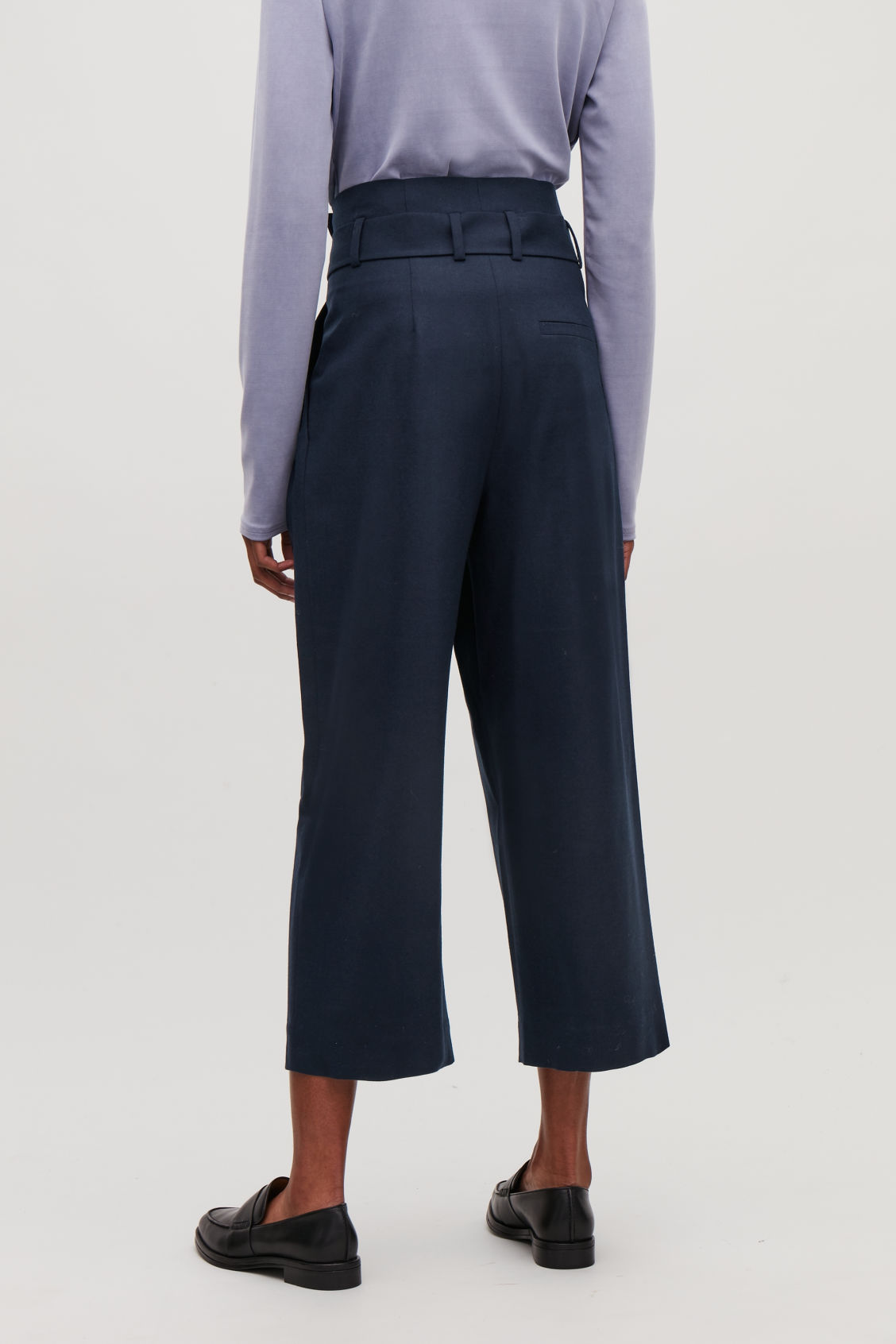 Model side image of Cos wool trousers with pleated waist  in blue