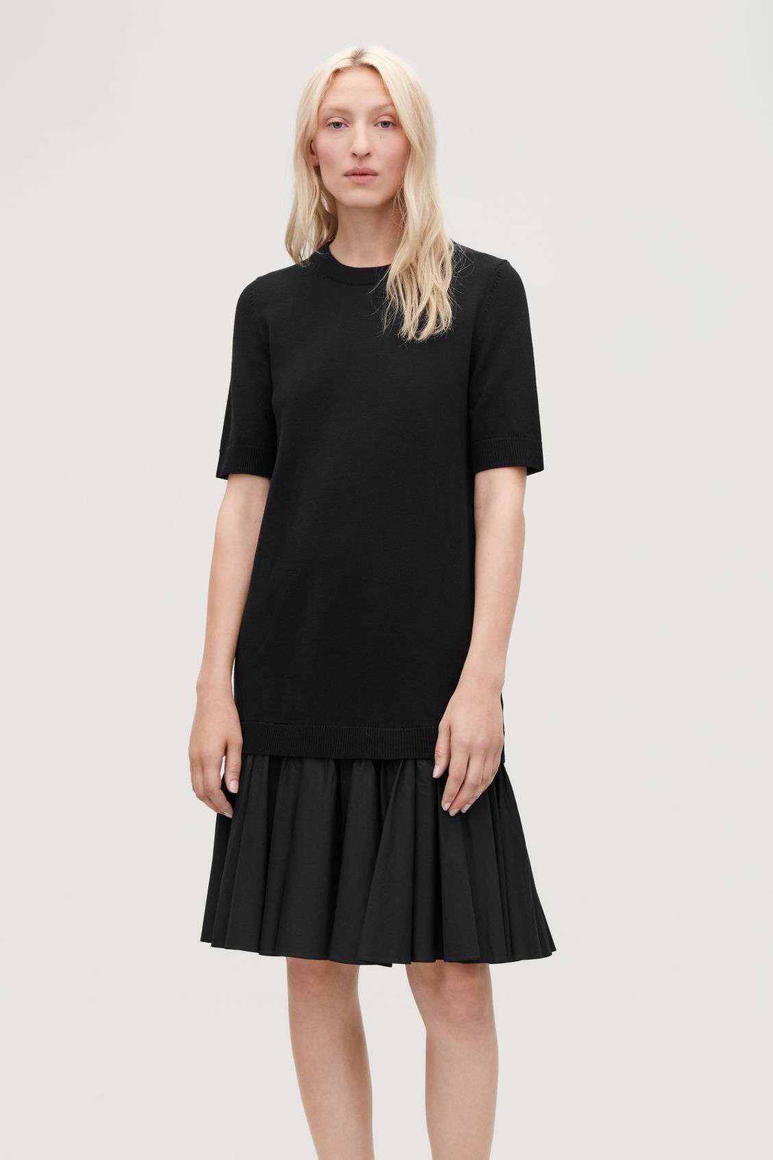 Model side image of Cos panelled cotton knit dress  in black