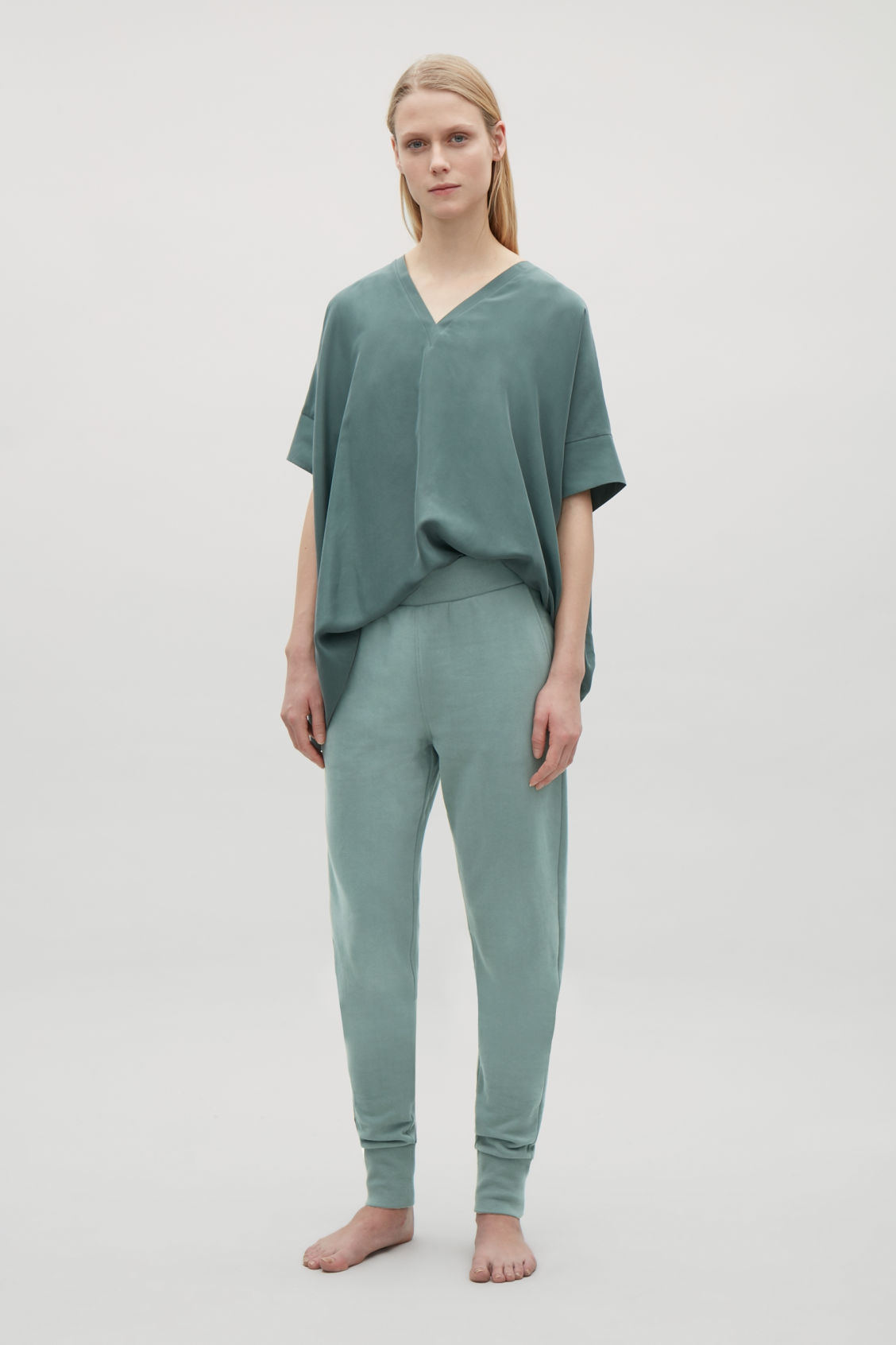 Model side image of Cos relaxed jersey trousers  in green