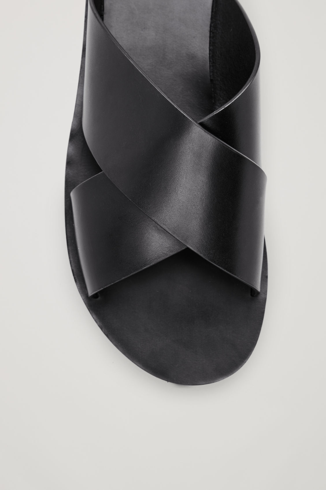 Model side image of Cos crossover leather sandals in black