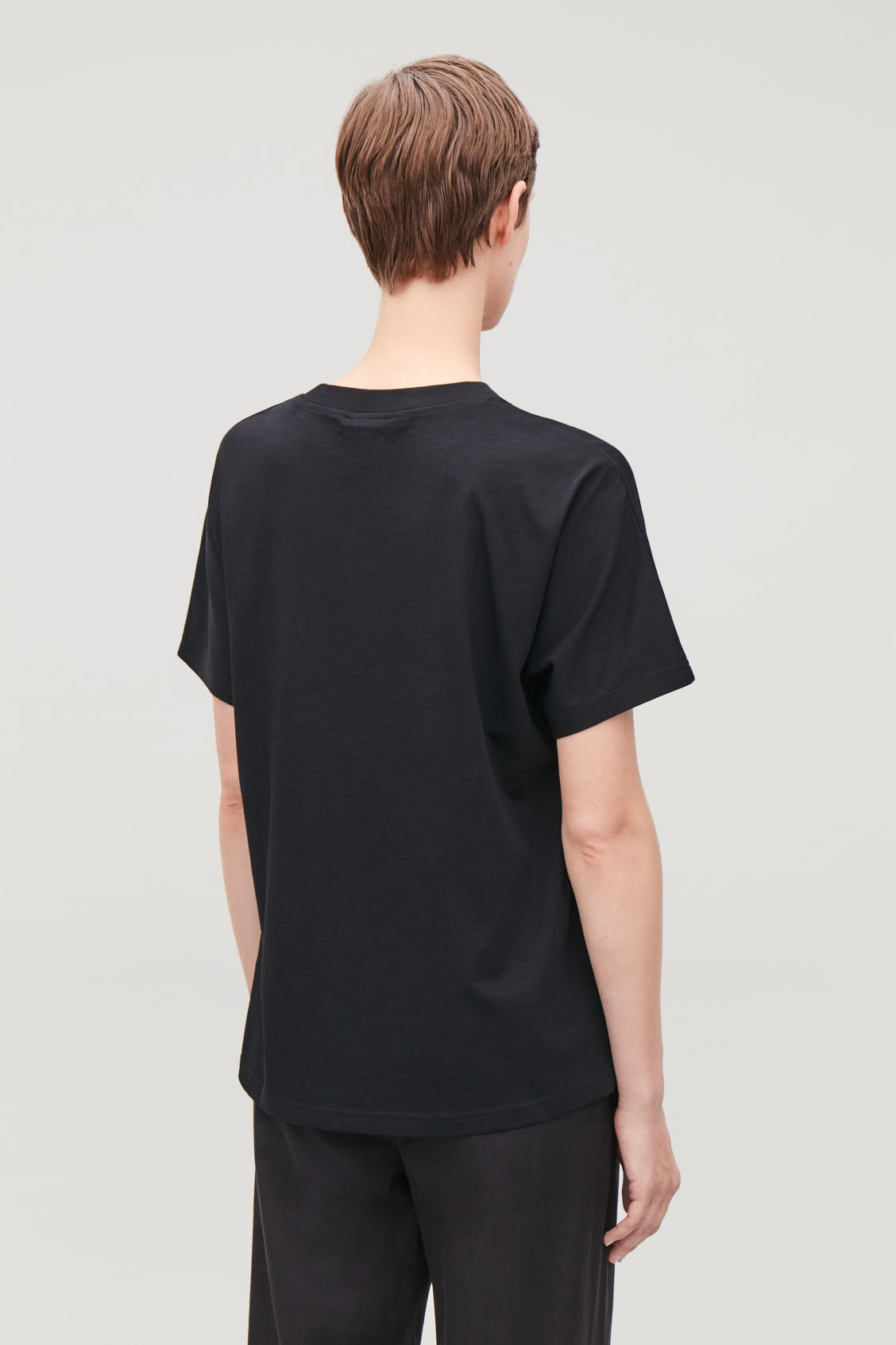 Model side image of Cos relaxed kimono-sleeved t-shirt in black