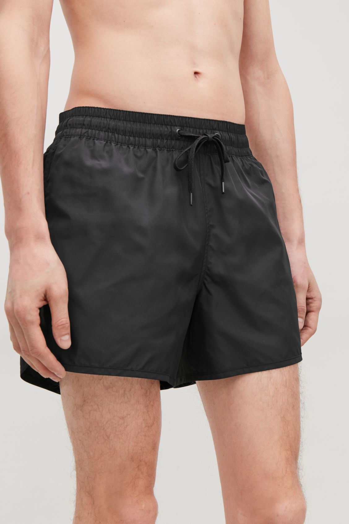 Model side image of Cos swim shorts in black