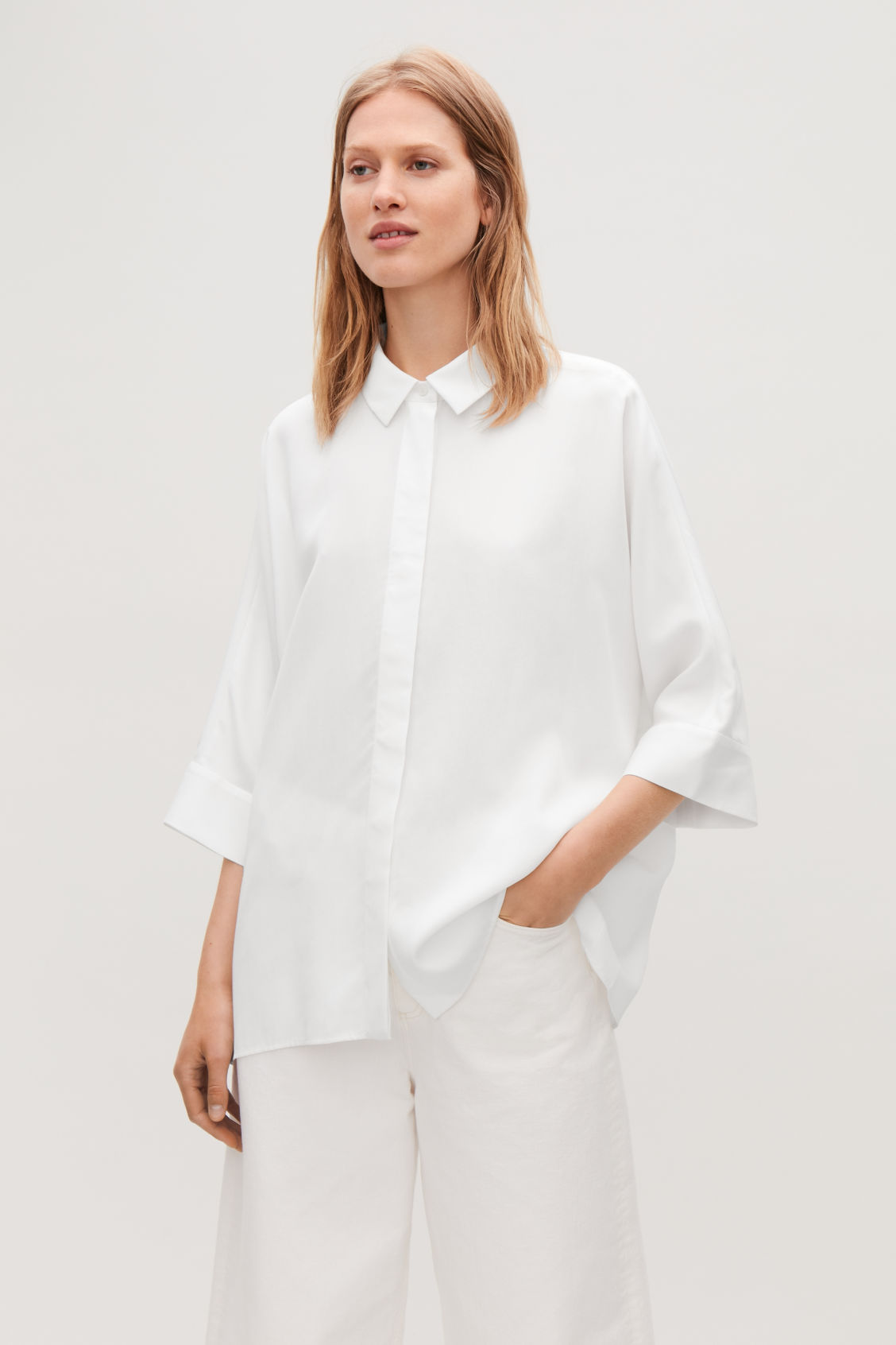 Model side image of Cos draped wide-fit shirt  in white