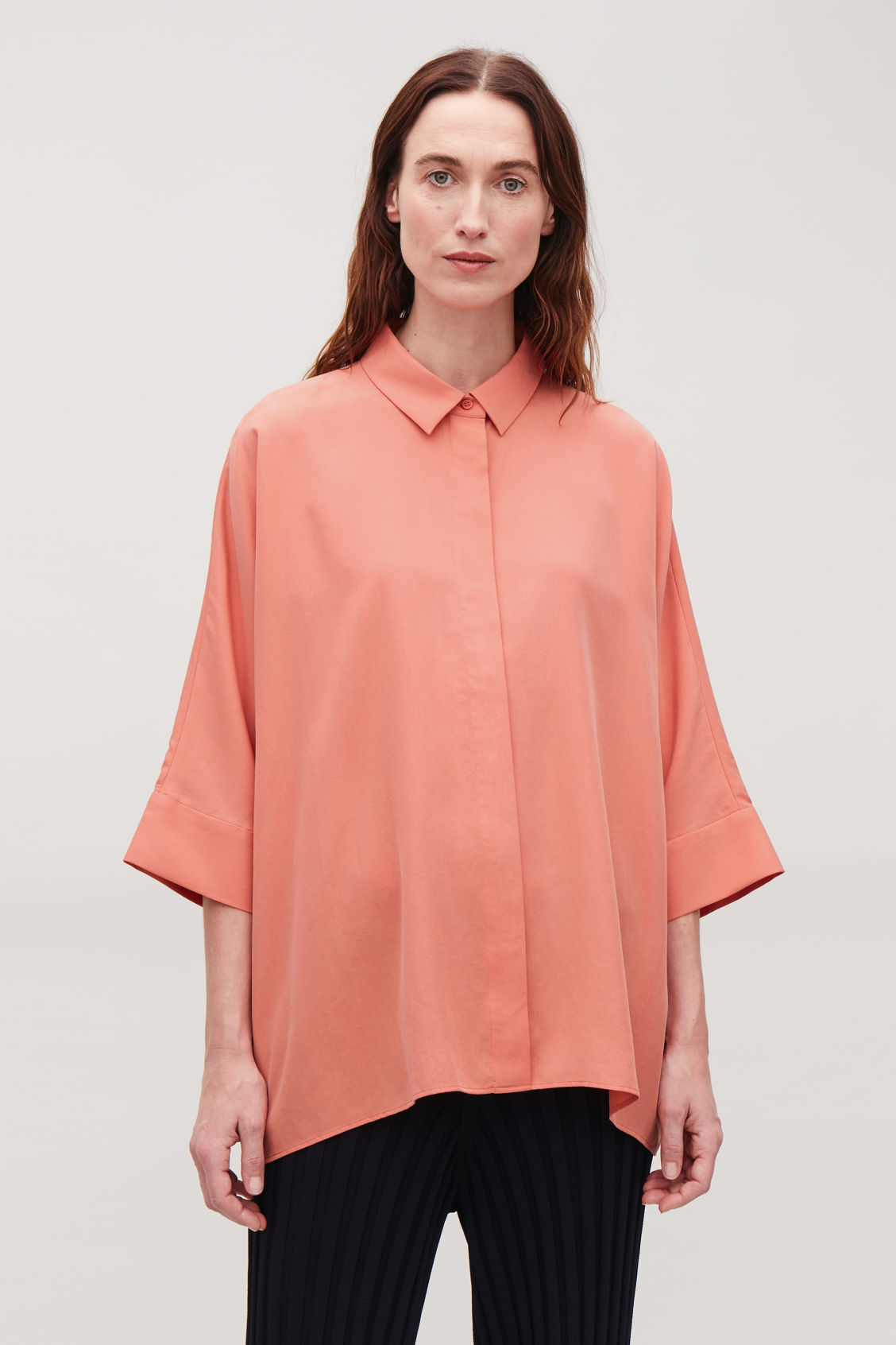 Model side image of Cos draped wide-fit shirt  in orange