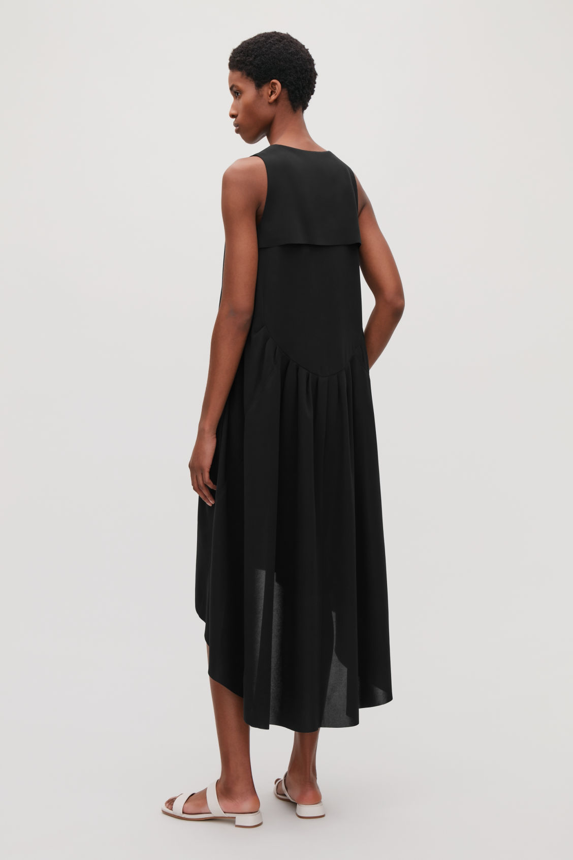 Model side image of Cos sleeveless dress with pleats in black