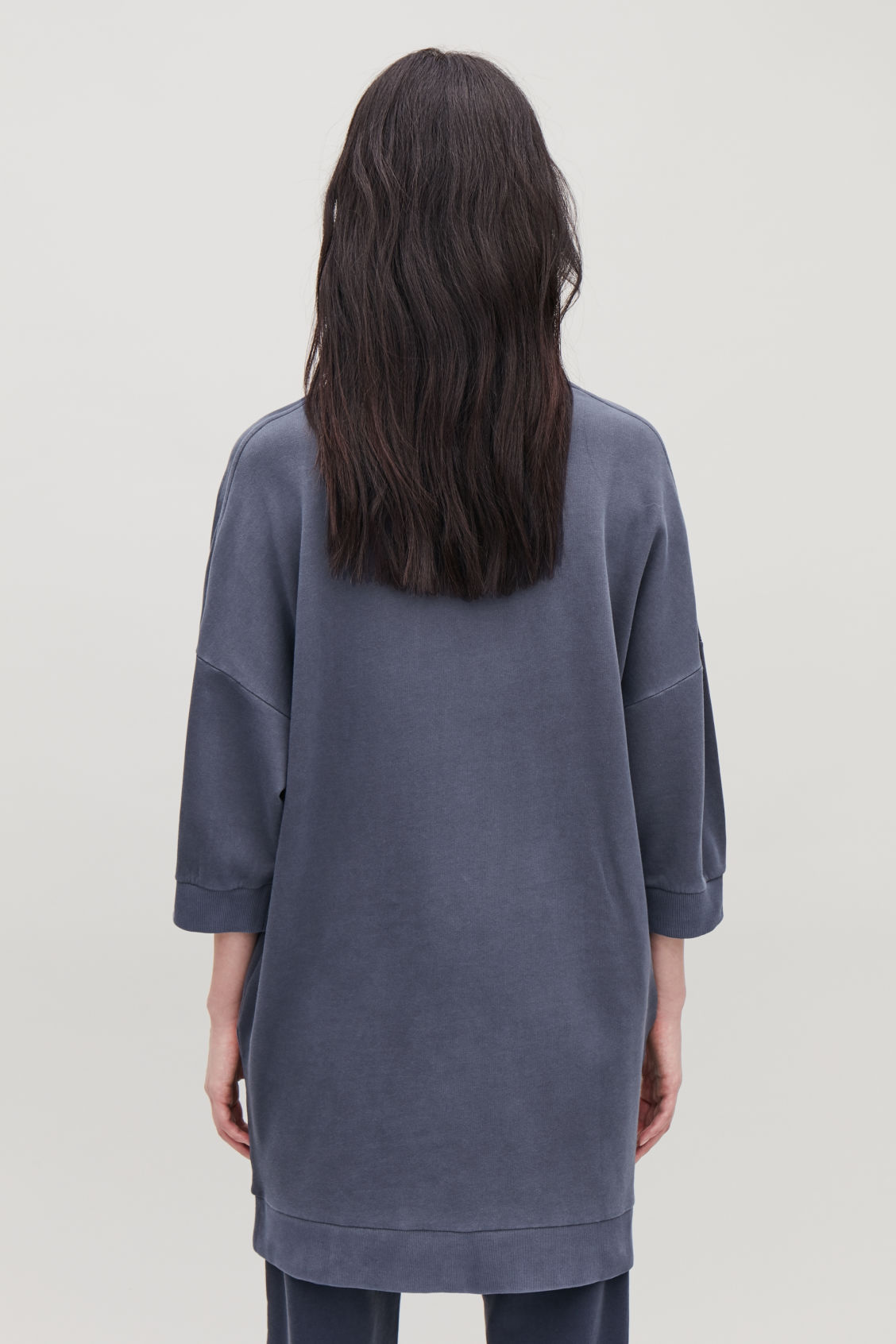 Model side image of Cos ¾-sleeved sweatshirt dress in blue