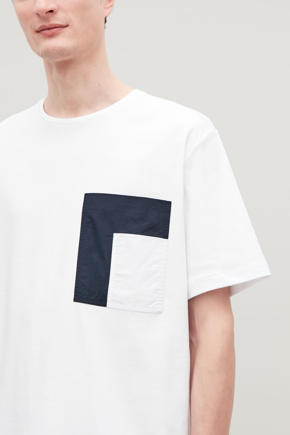 Model side image of Cos t-shirt with contrast pocket in white