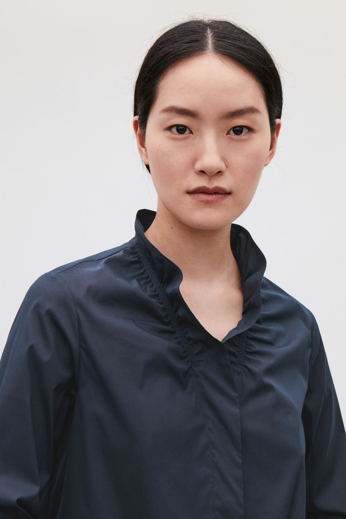 Model side image of Cos buttoned blouse with frill v-neck in blue