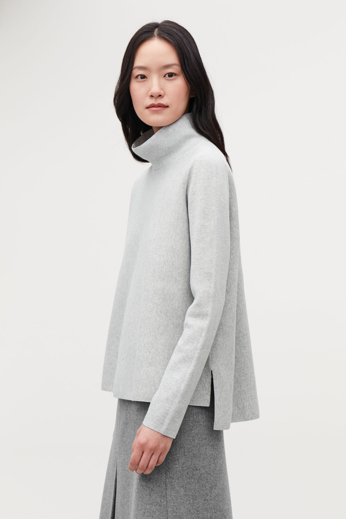 Model side image of Cos high-neck a-line jumper in grey