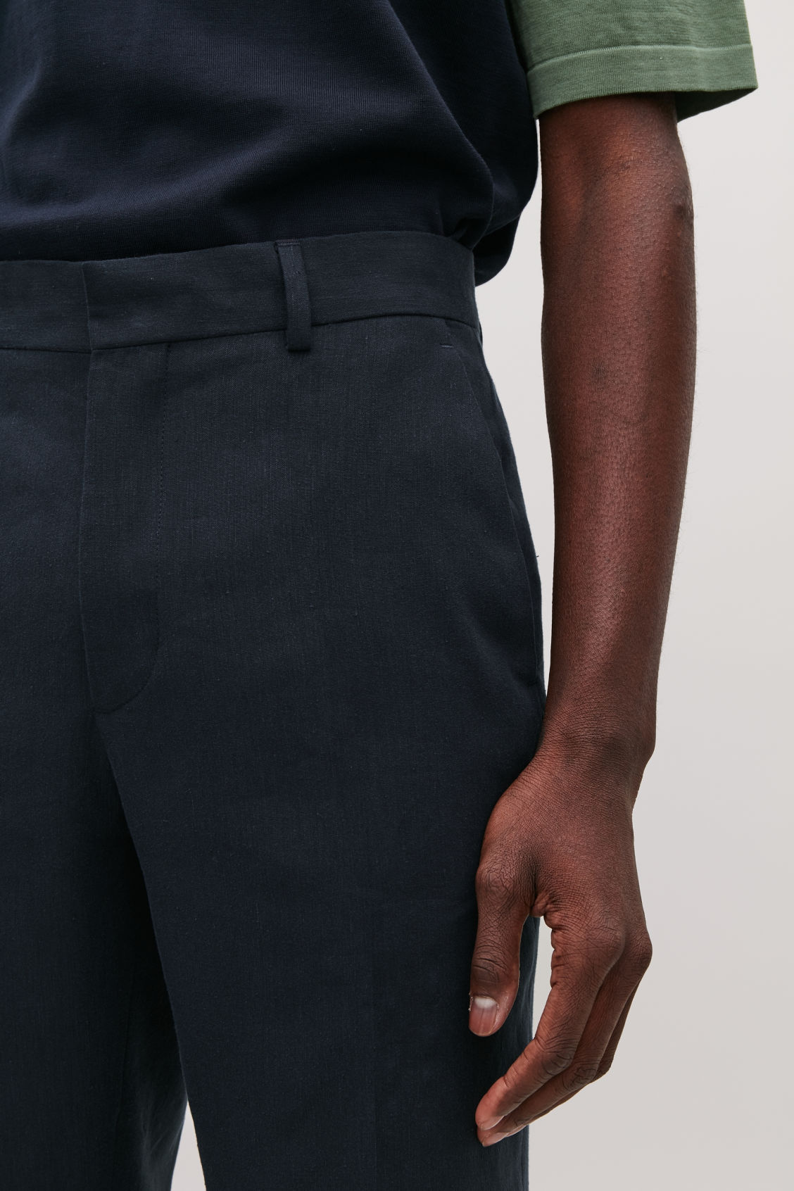 Model side image of Cos slim-fit linen trousers in blue
