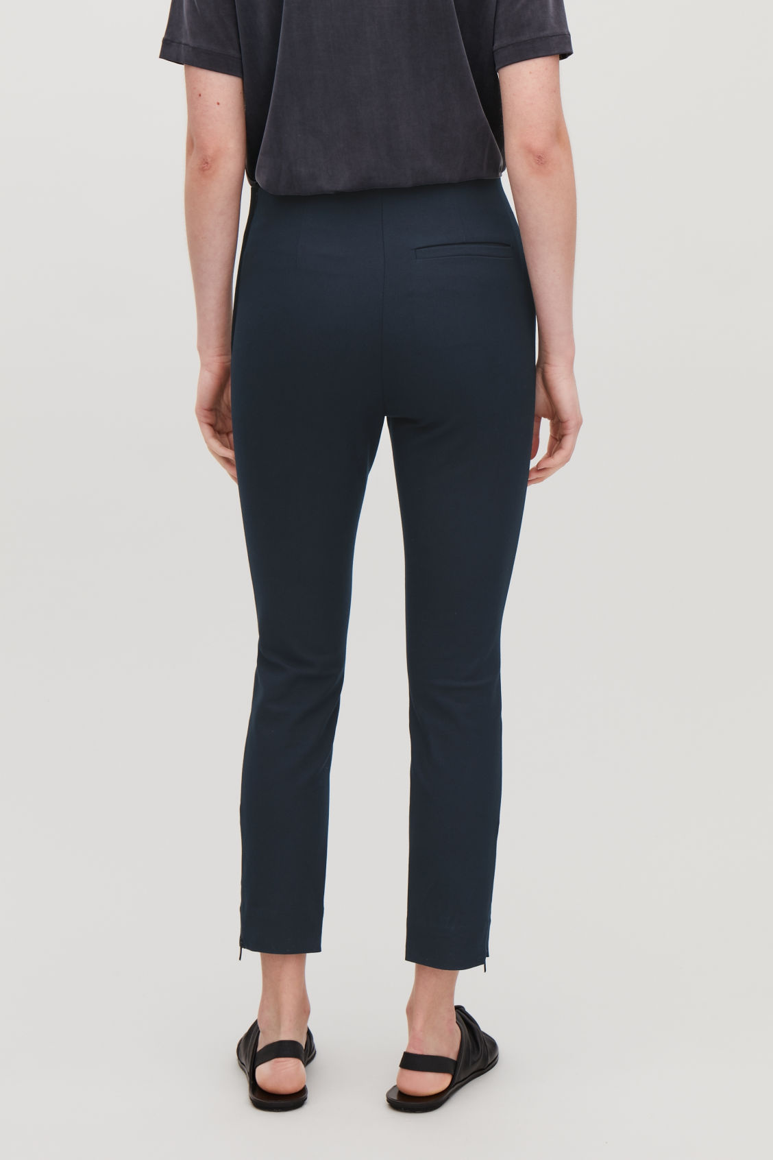 Model side image of Cos slim-fit trousers with ankle zips  in blue