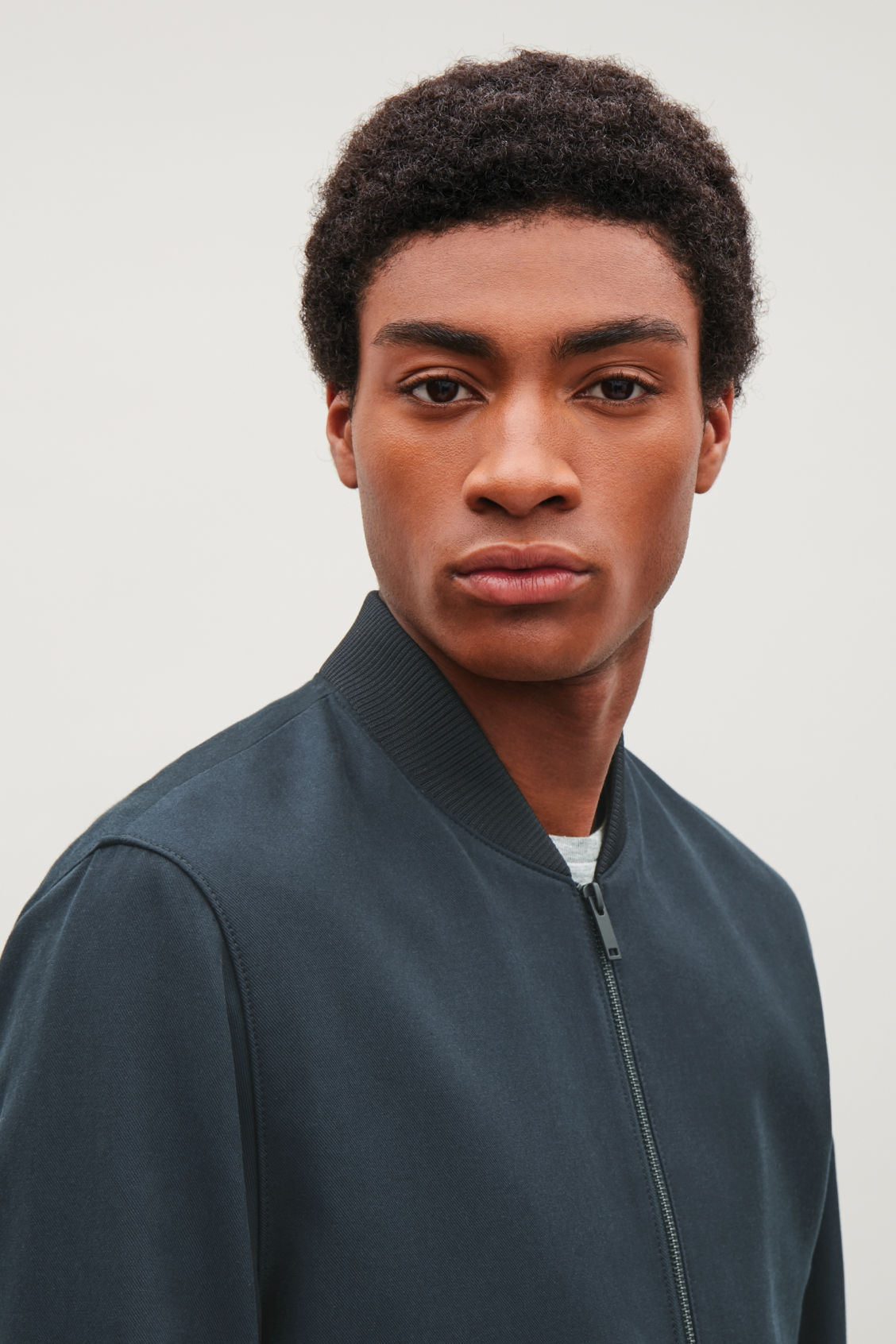 Model side image of Cos cotton bomber jacket in blue