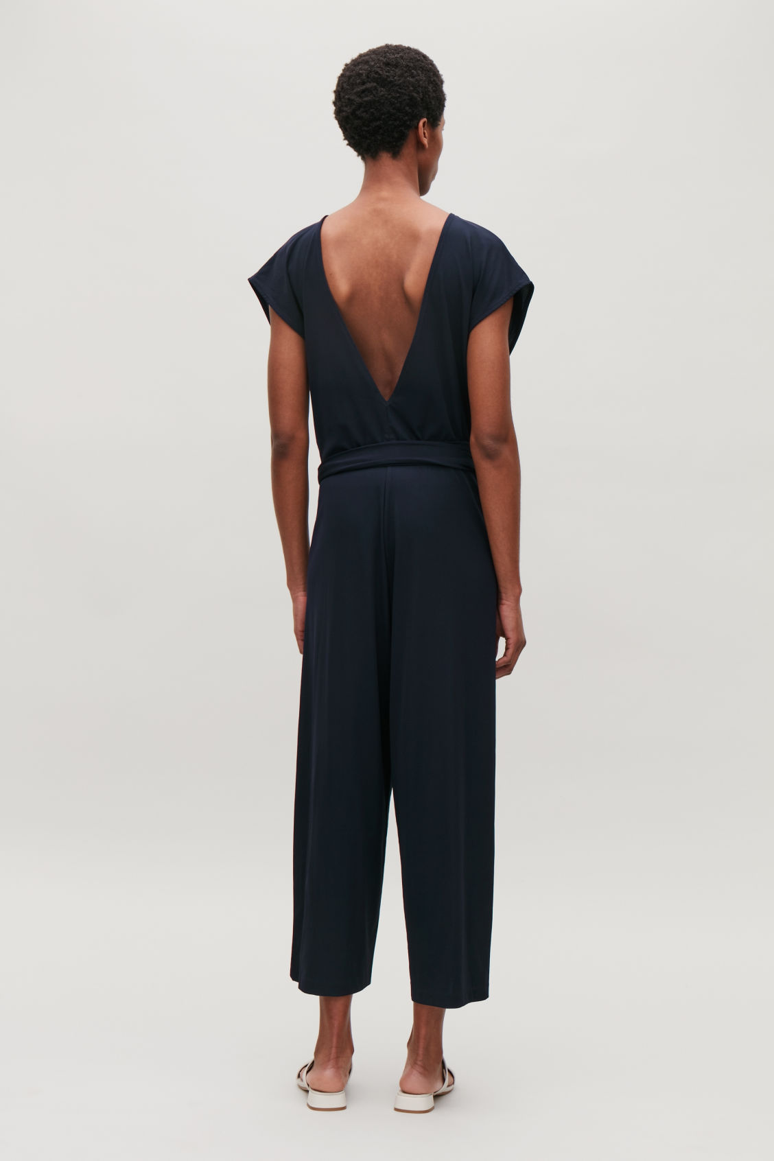 d0fb2fbdaad Model side image of Cos wrap-front jersey jumpsuit in blue