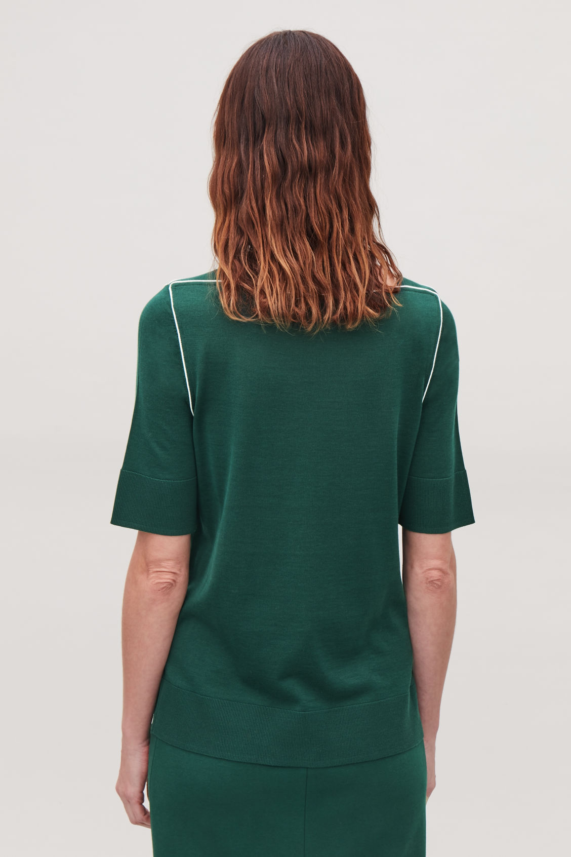Model side image of Cos silk-blend knit top with piping in green