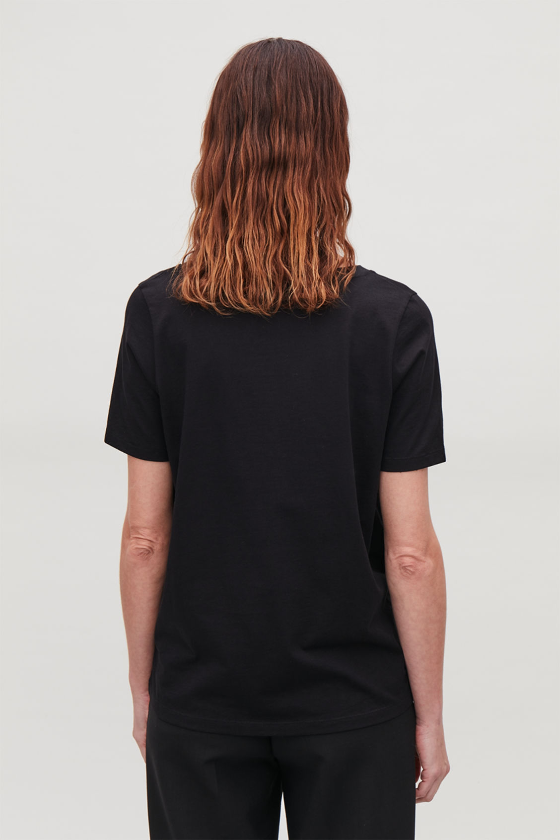 Model side image of Cos wide v-neck t-shirt in black