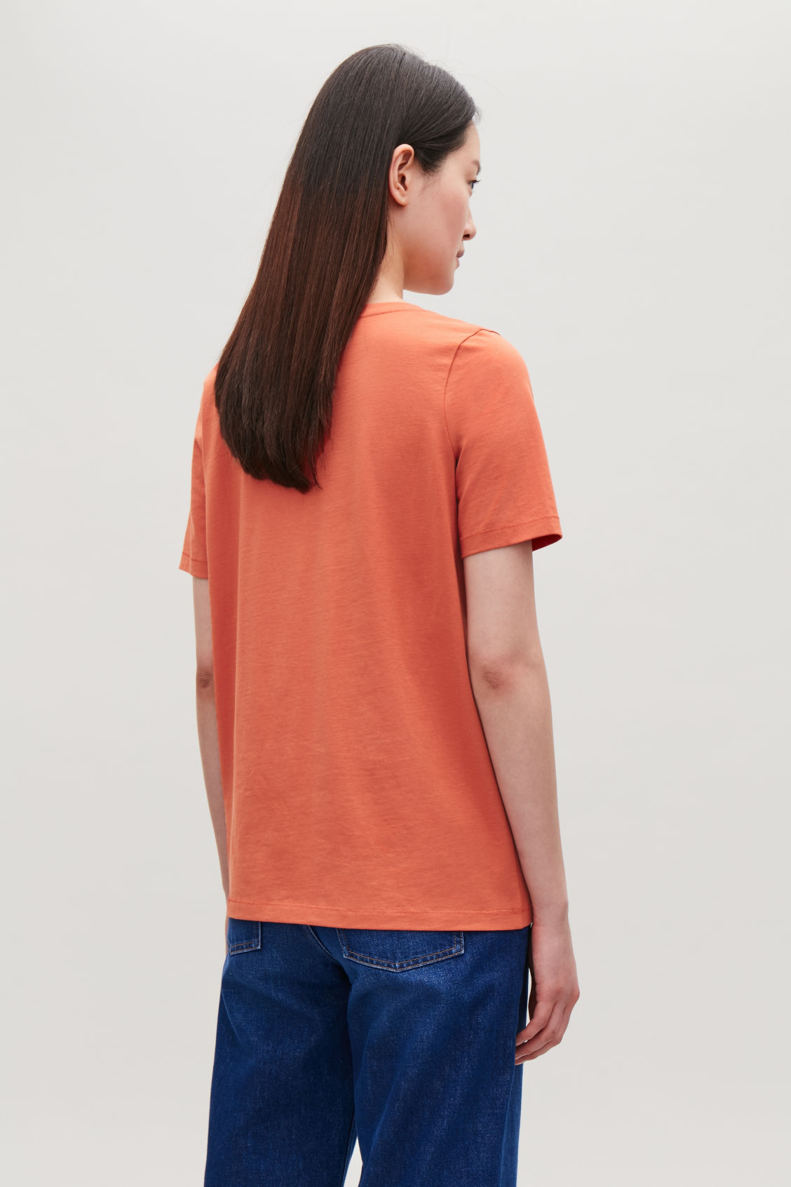 Model side image of Cos wide v-neck t-shirt in red