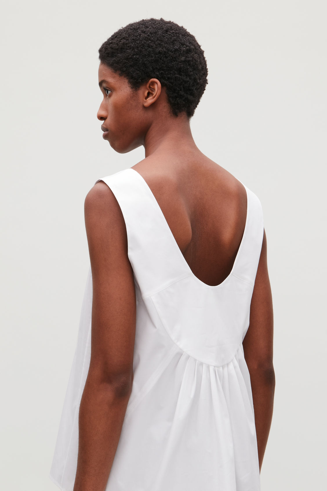Model side image of Cos low v-neck pleated top in white