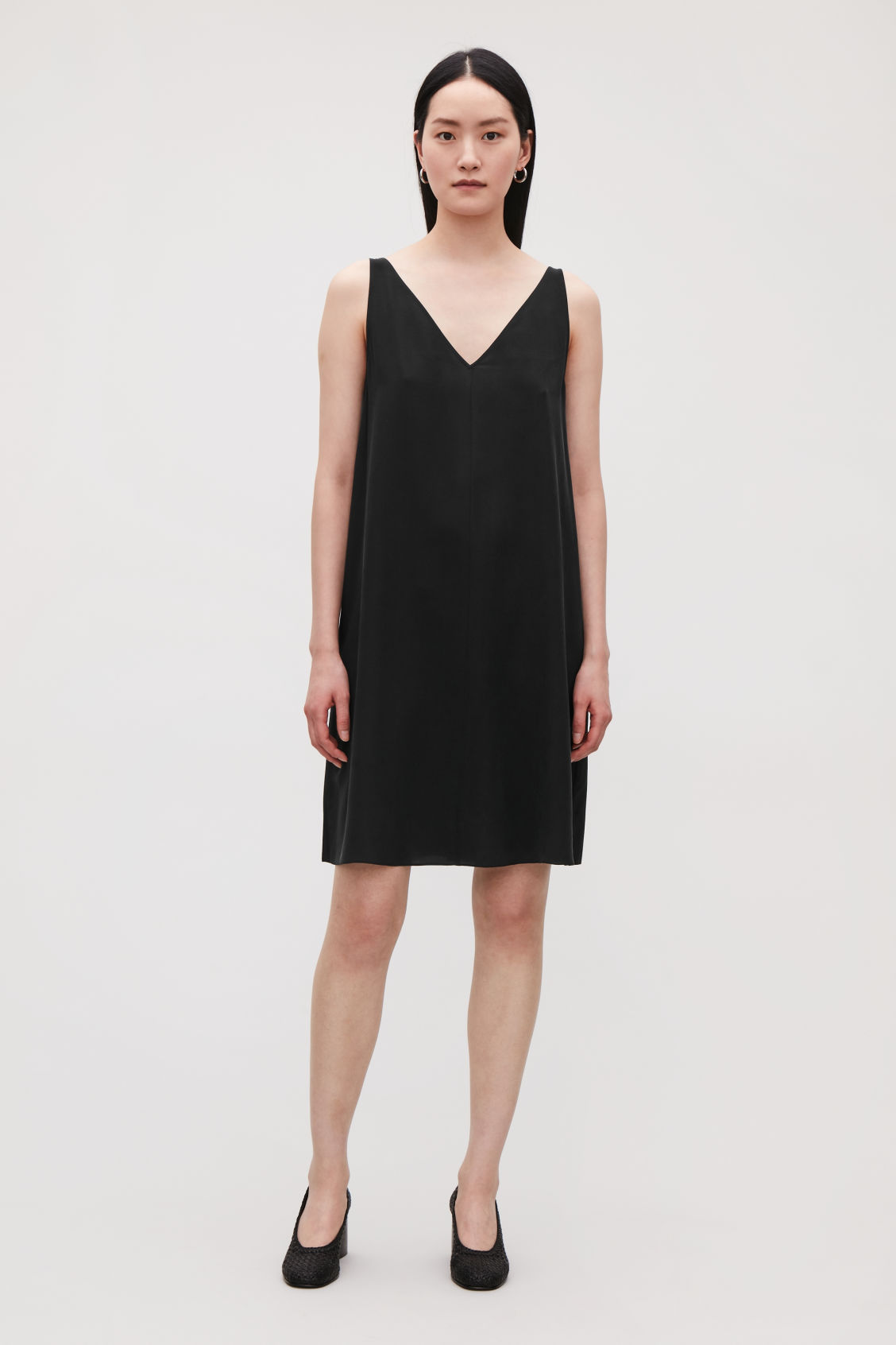 Model side image of Cos sleeveless silk dress in black
