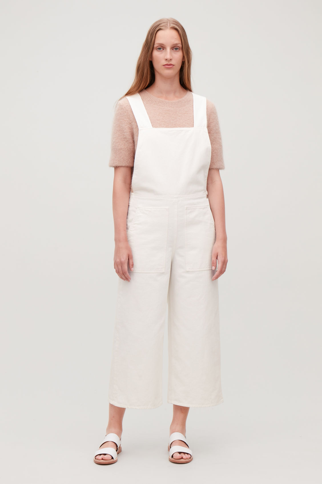Model side image of Cos denim dungarees in white
