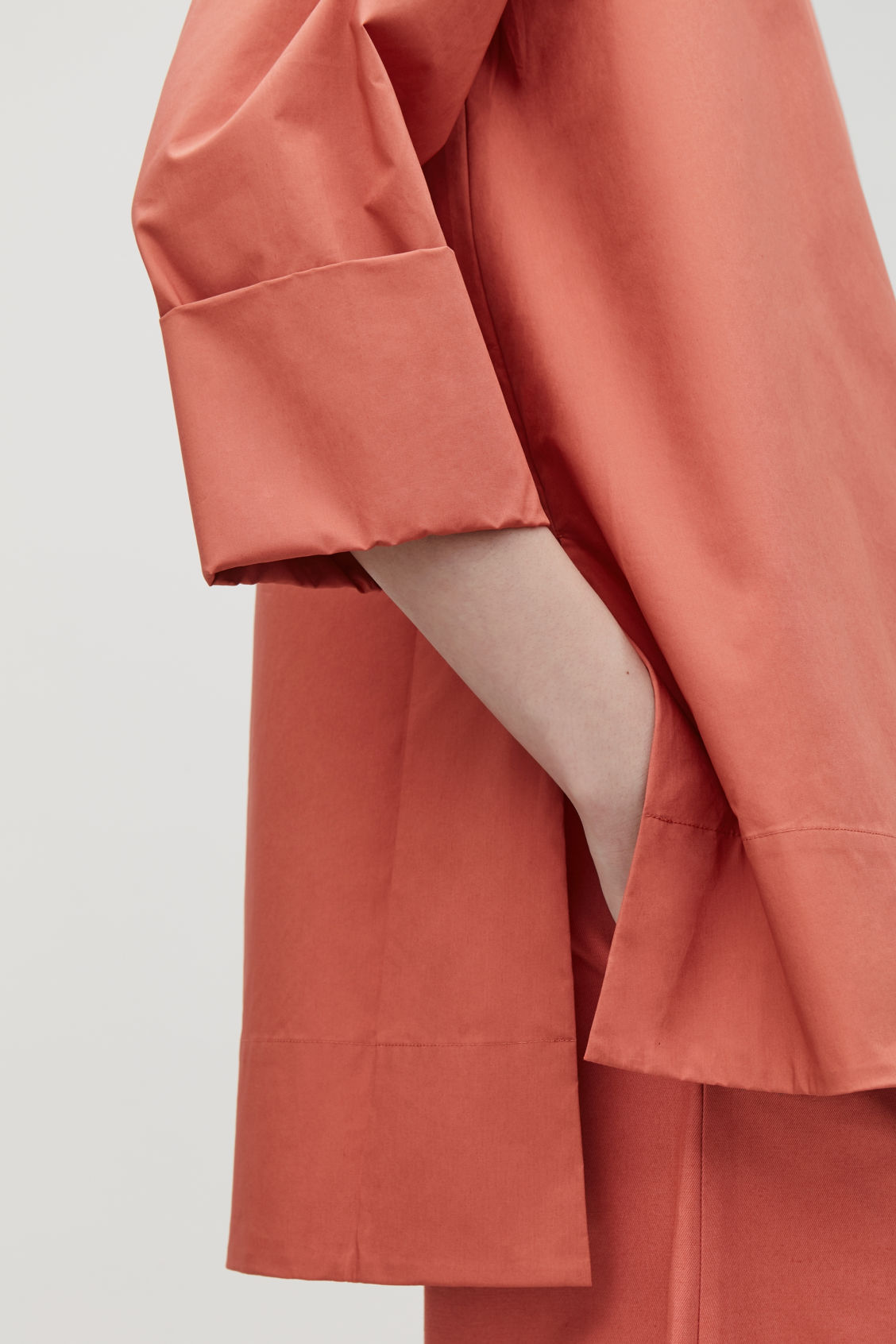 Model side image of Cos a-line top with folded cuffs in orange