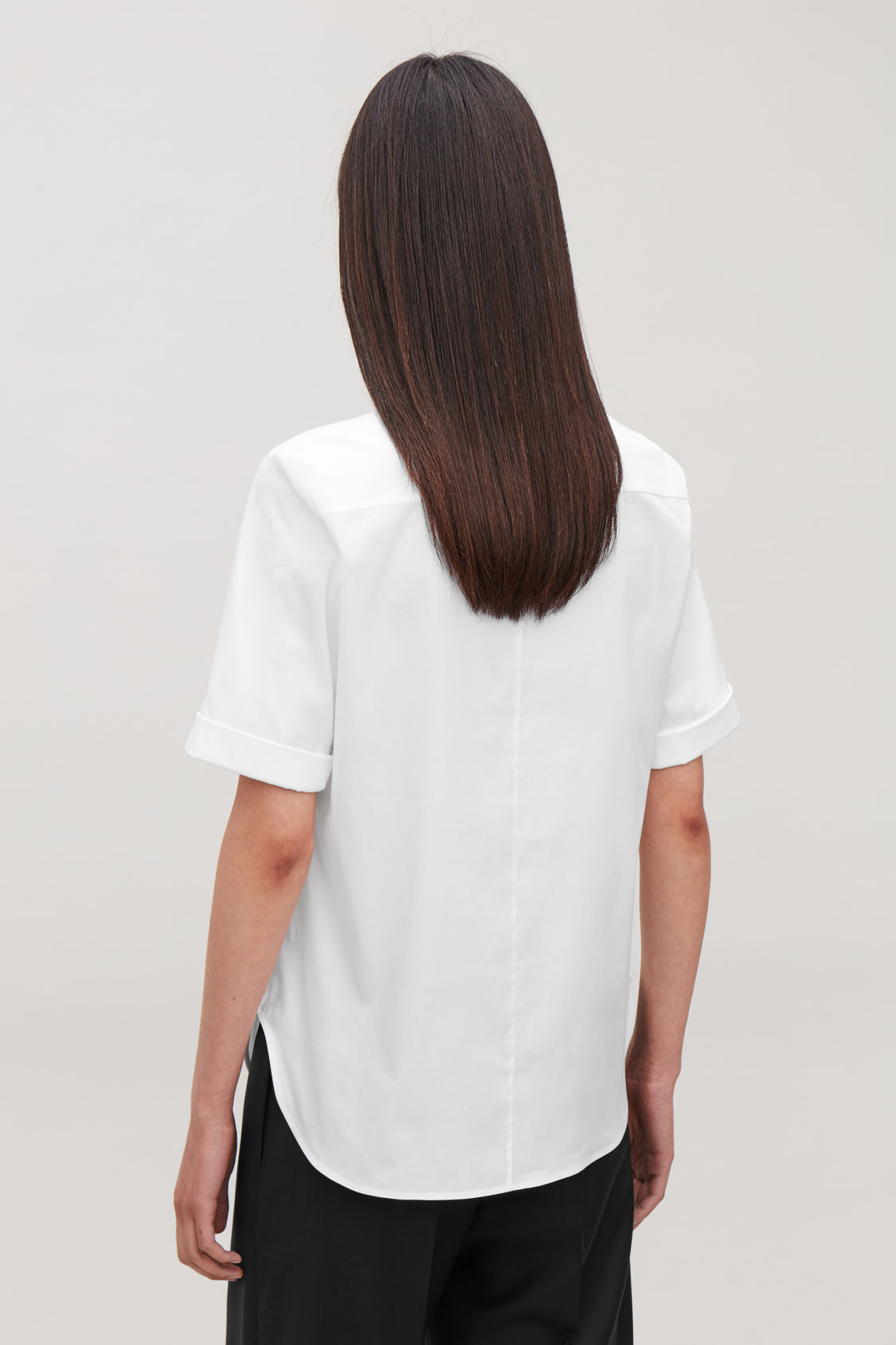 Model side image of Cos slim shirt with turn-up sleeves in white