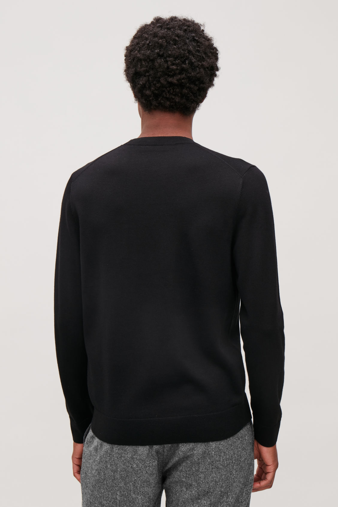 Model side image of Cos merino wool jumper in black