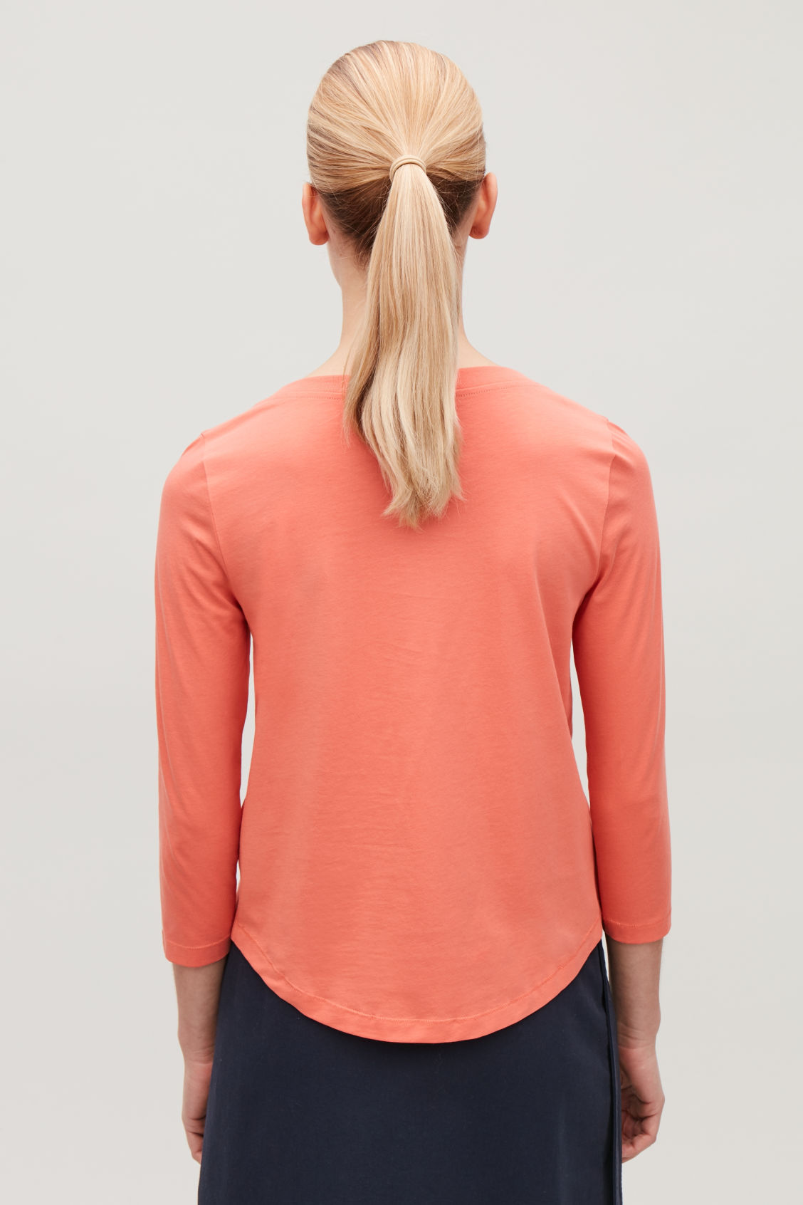 Model side image of Cos ¾-sleeved cotton top in orange