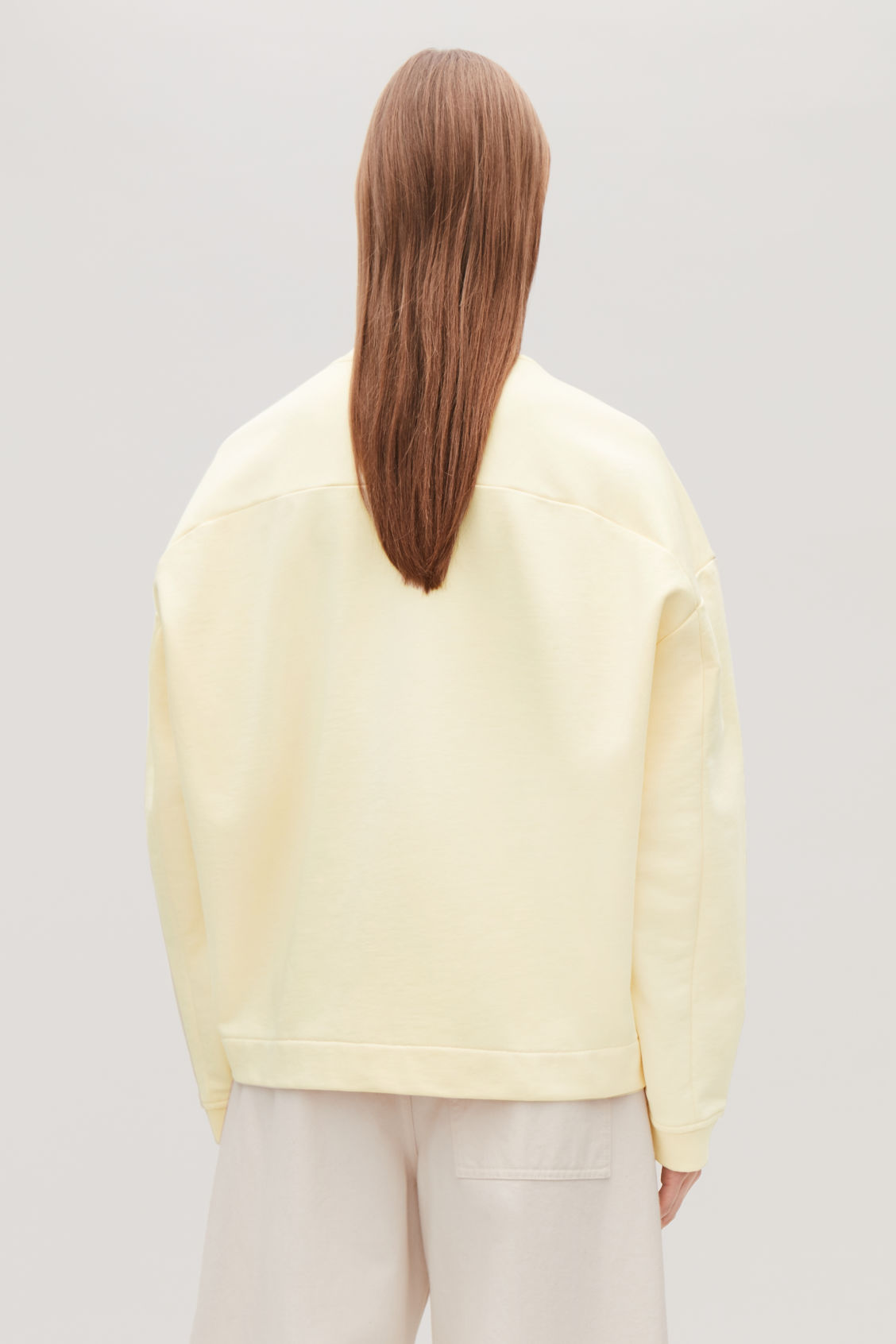 Model side image of Cos cocoon recycled cotton sweatshirt in yellow