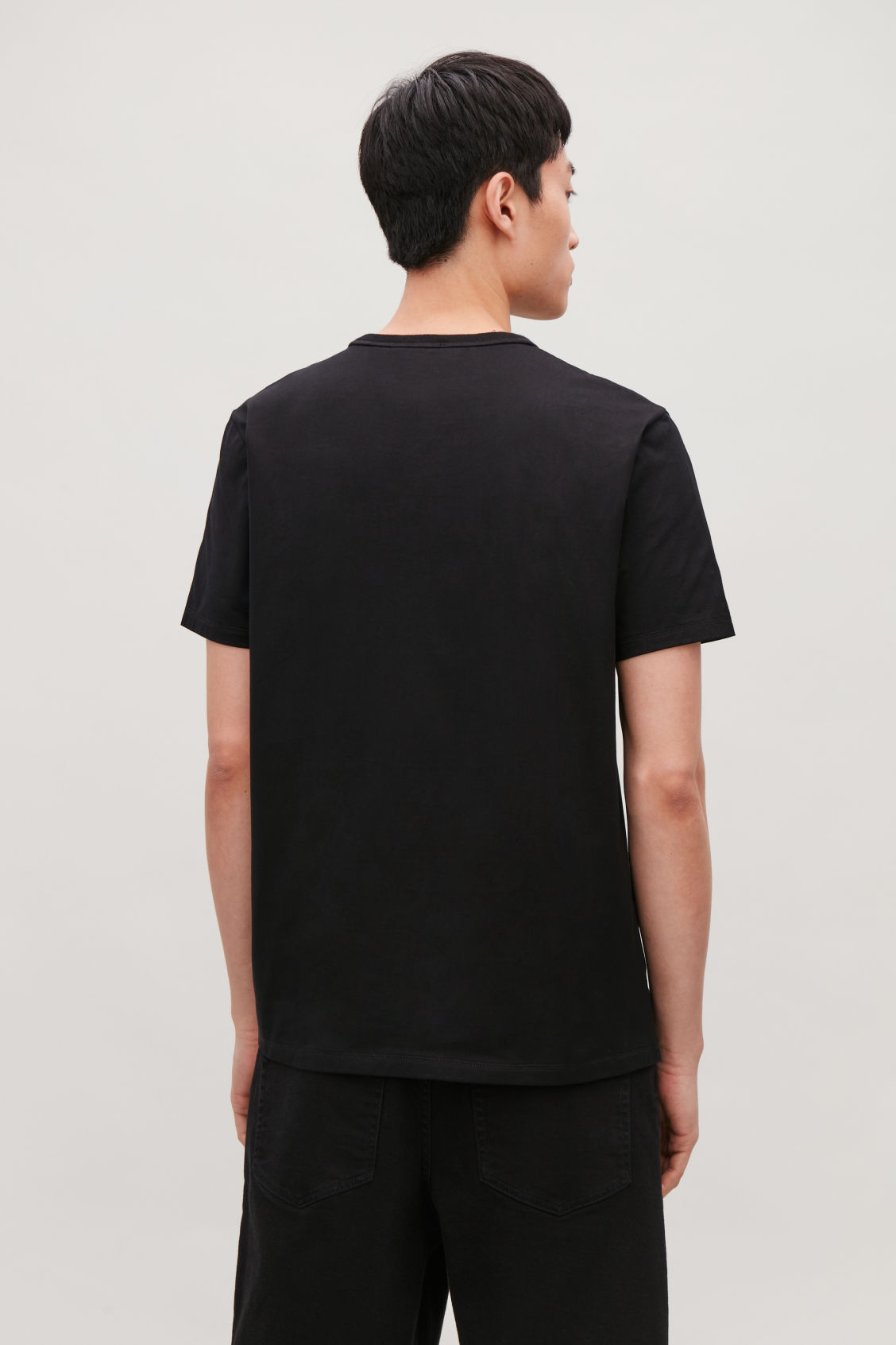 Model side image of Cos ribbed-neck cotton t-shirt in black