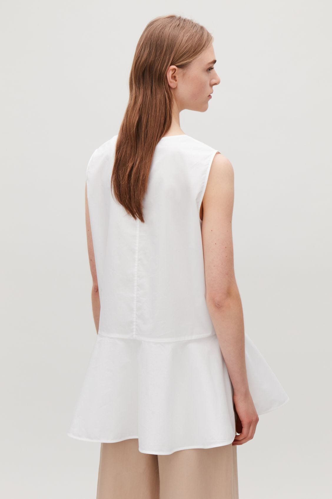 Model side image of Cos flared sleeveless cotton top in white
