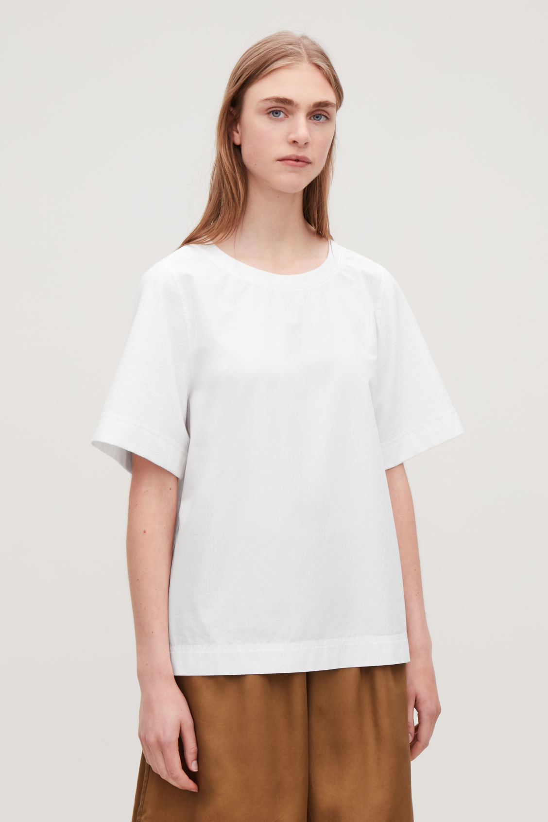 Model side image of Cos top with textured sleeves in white