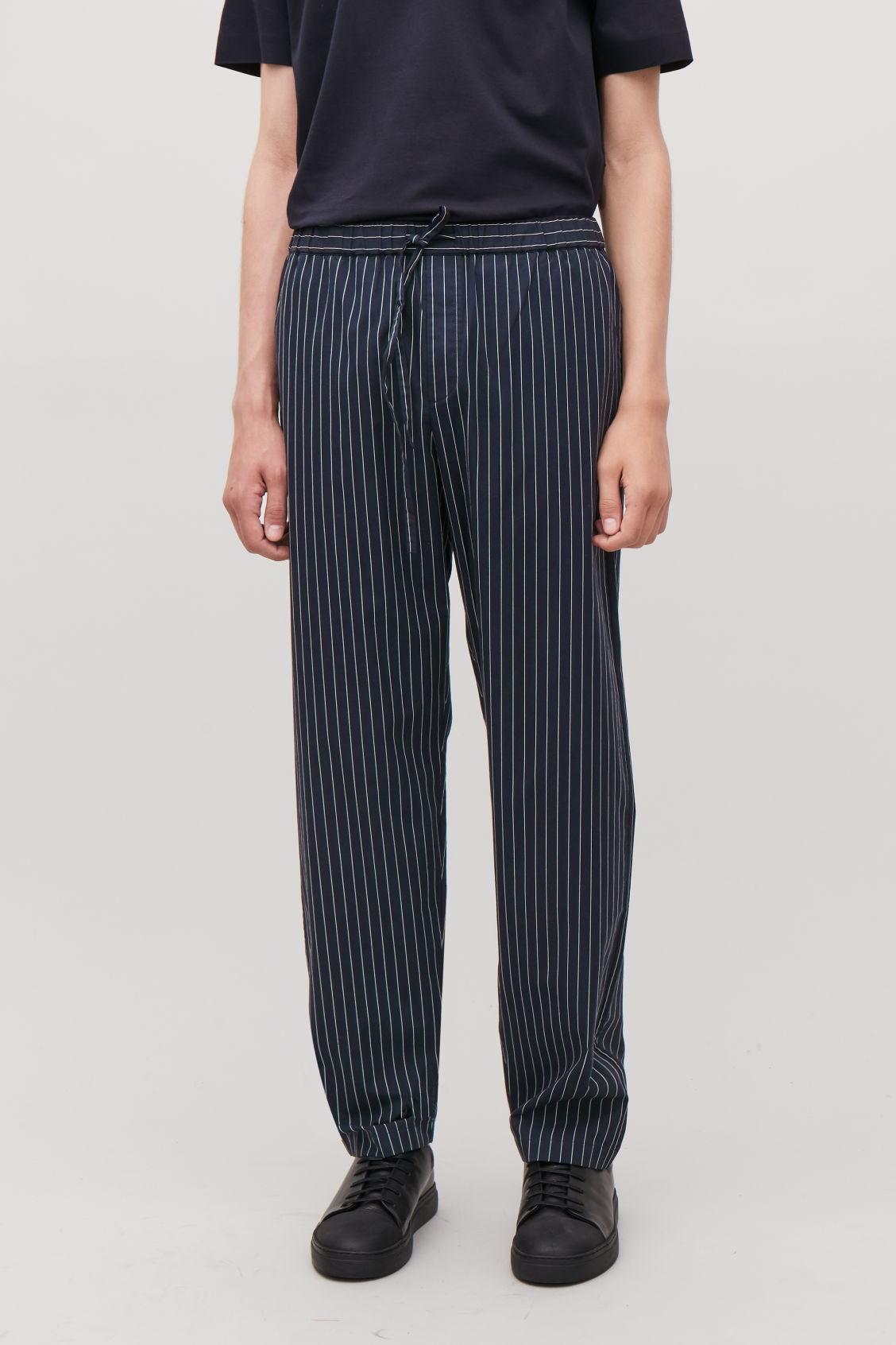 Model side image of Cos pinstriped pyjama trousers in blue