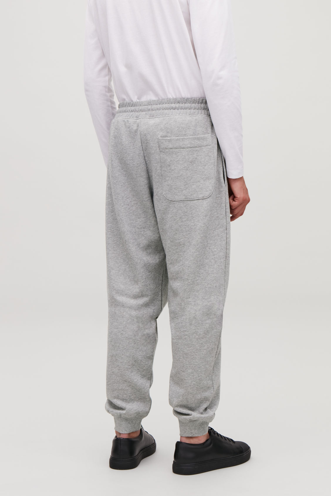 Model side image of Cos jersey jogging trousers in grey