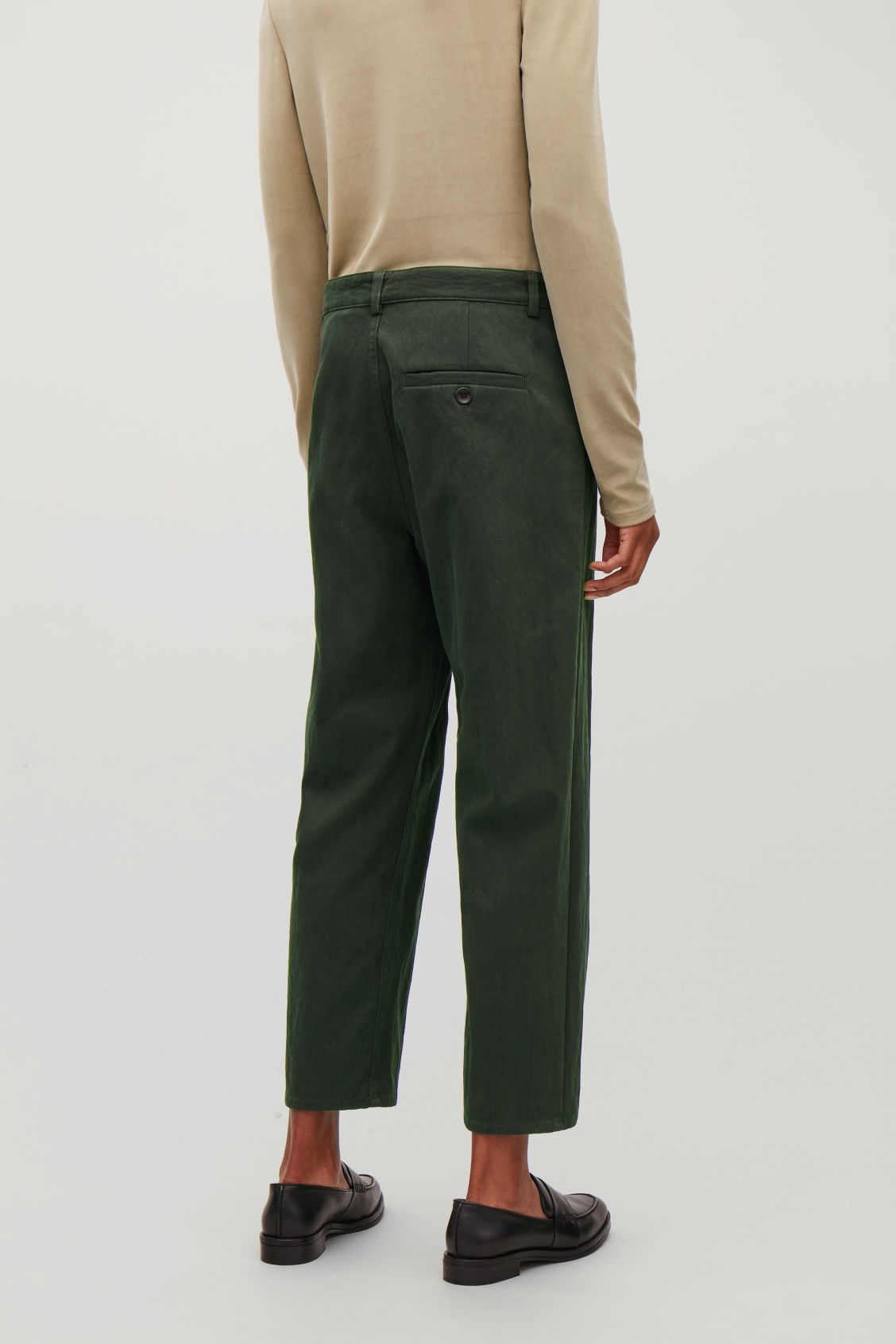 Model side image of Cos relaxed button-up chinos in green