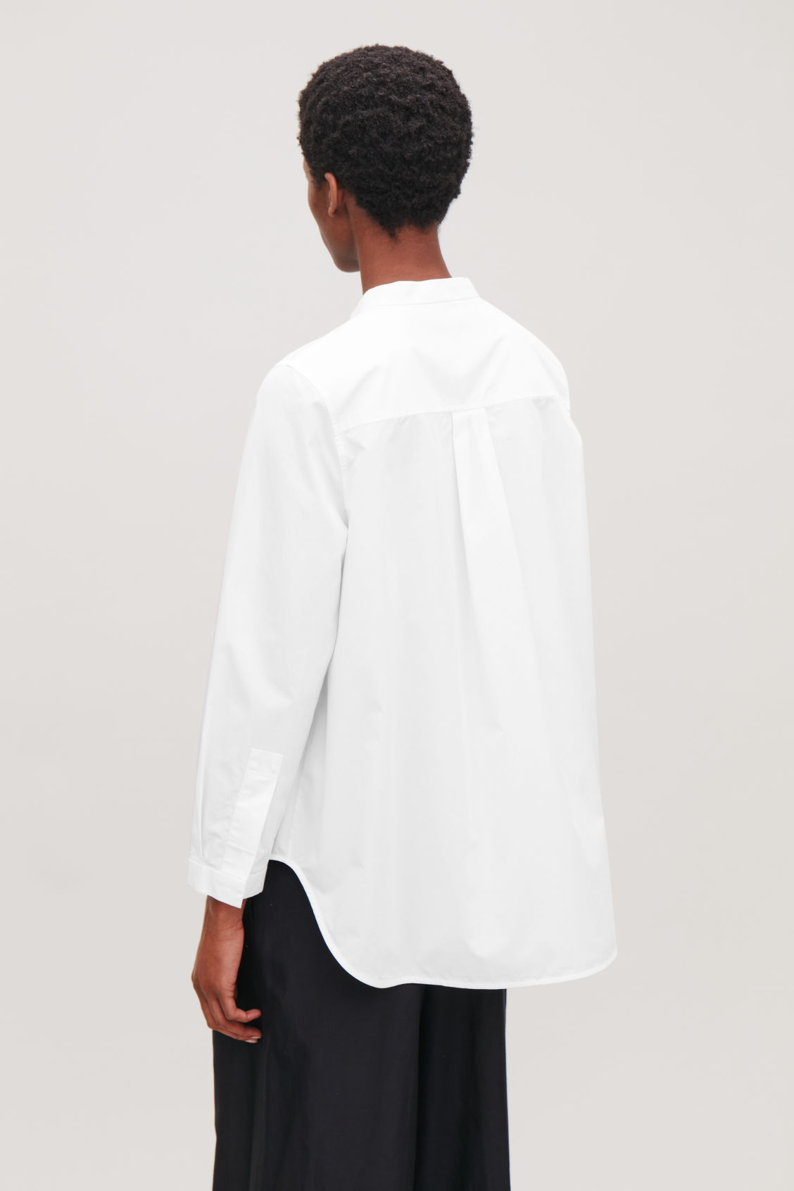 Model side image of Cos voluminous shirt with pockets in white