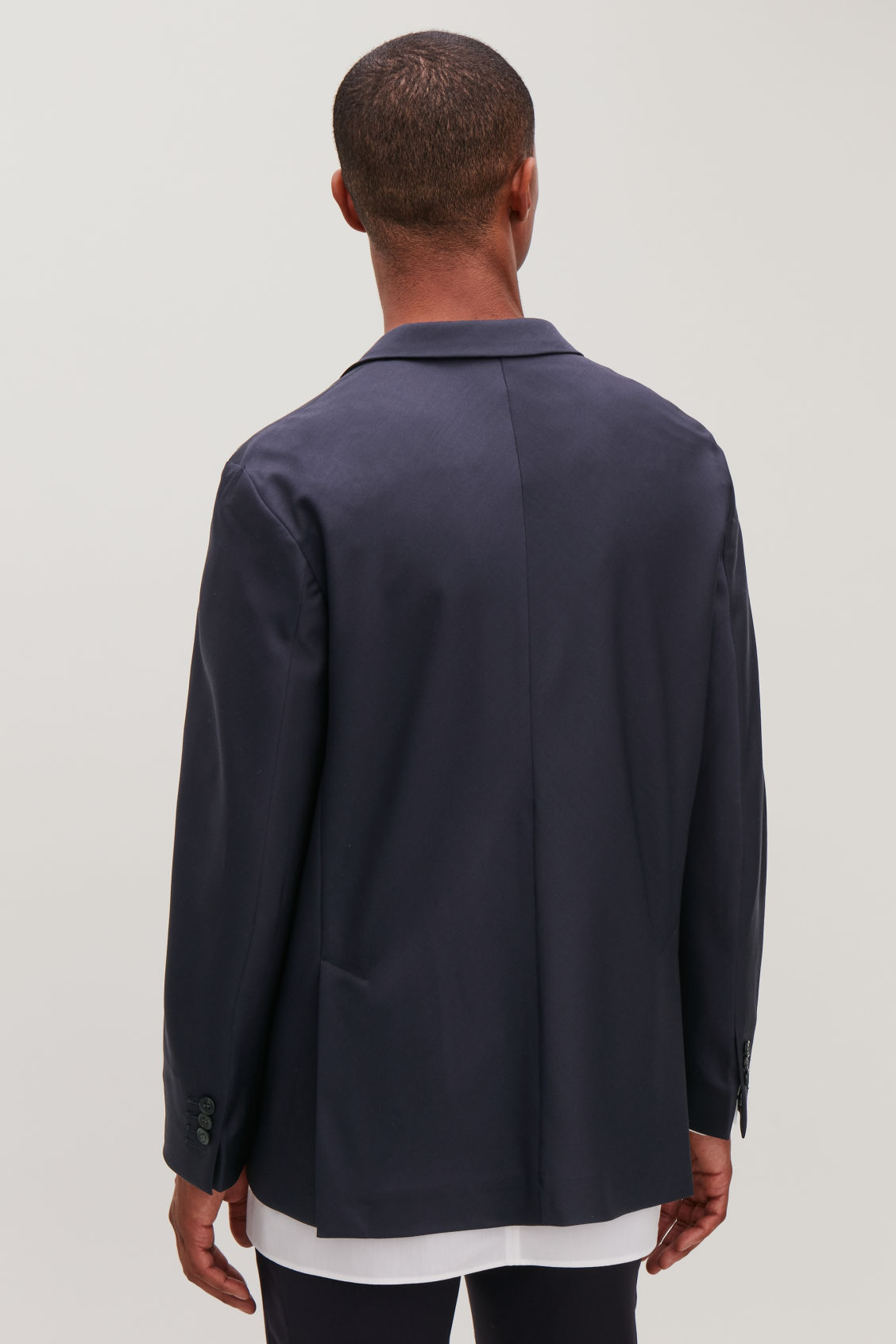 Model side image of Cos boxy-fit wool blazer in blue