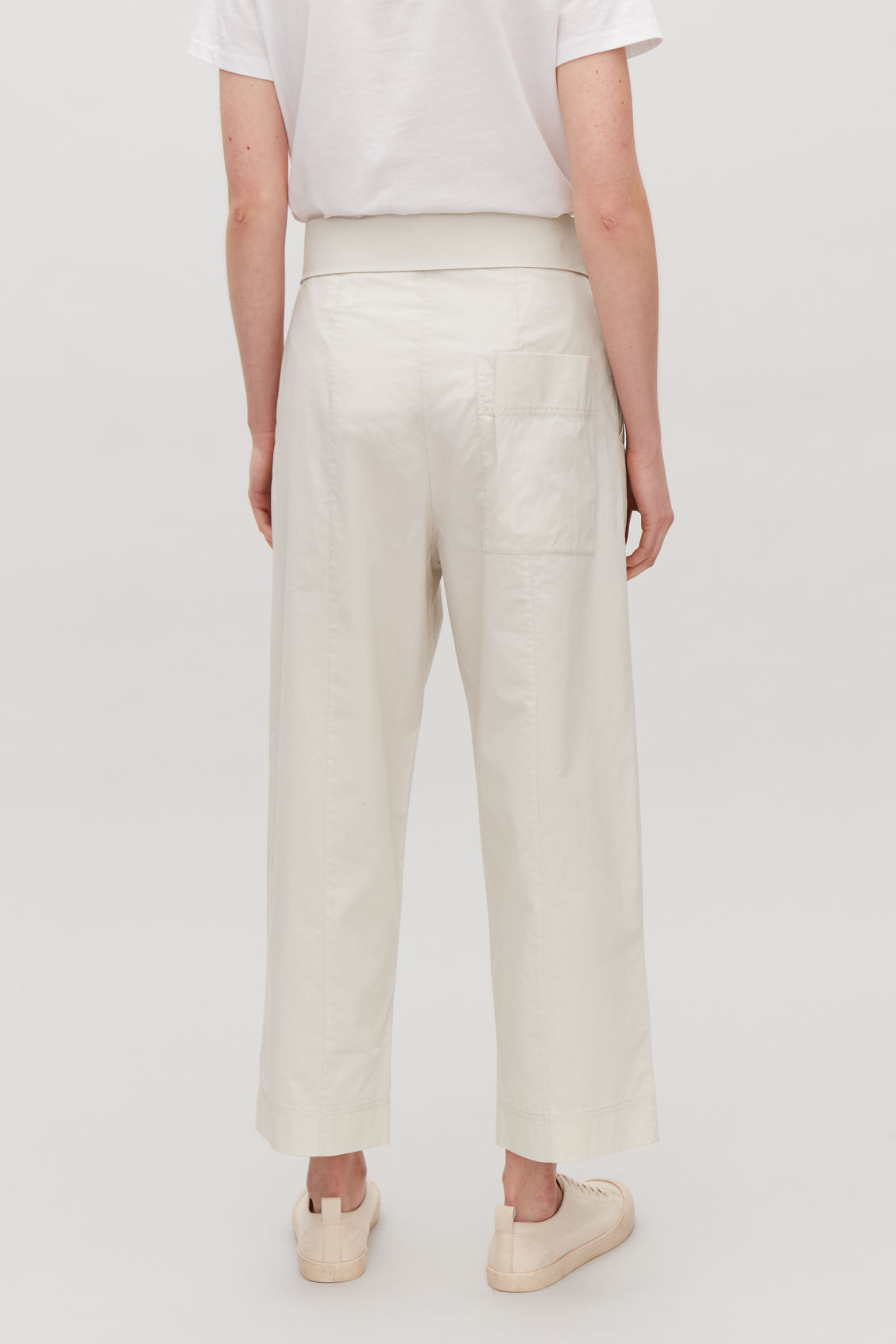 Model side image of Cos trousers with folded waistband in beige