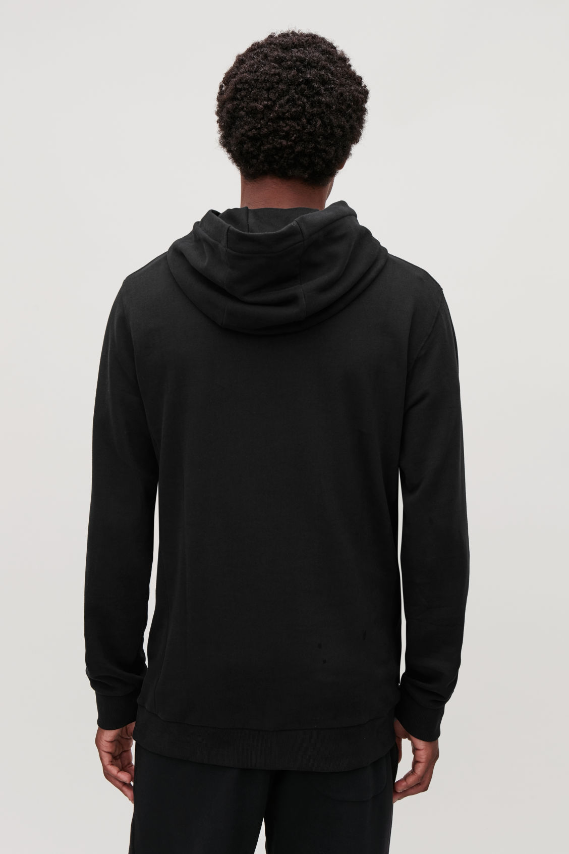Model side image of Cos cotton hooded jumper in black
