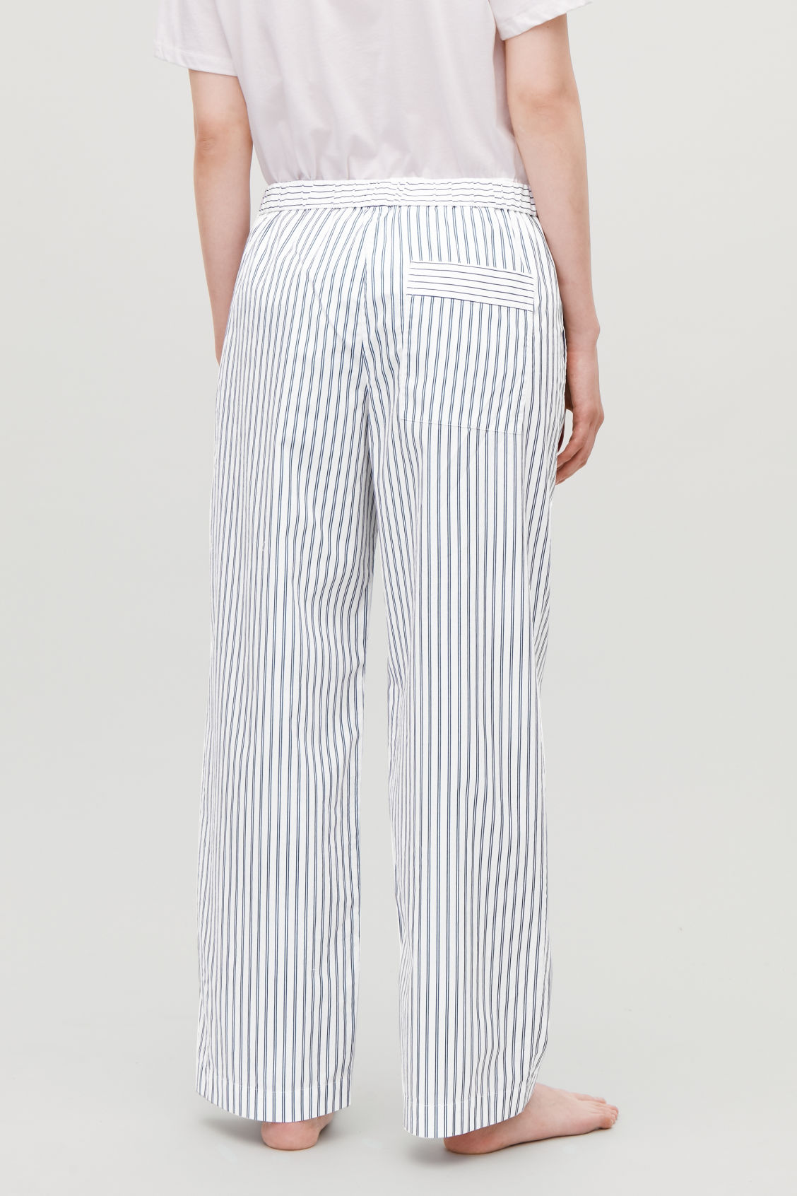Model side image of Cos slim striped pyjama trousers in blue