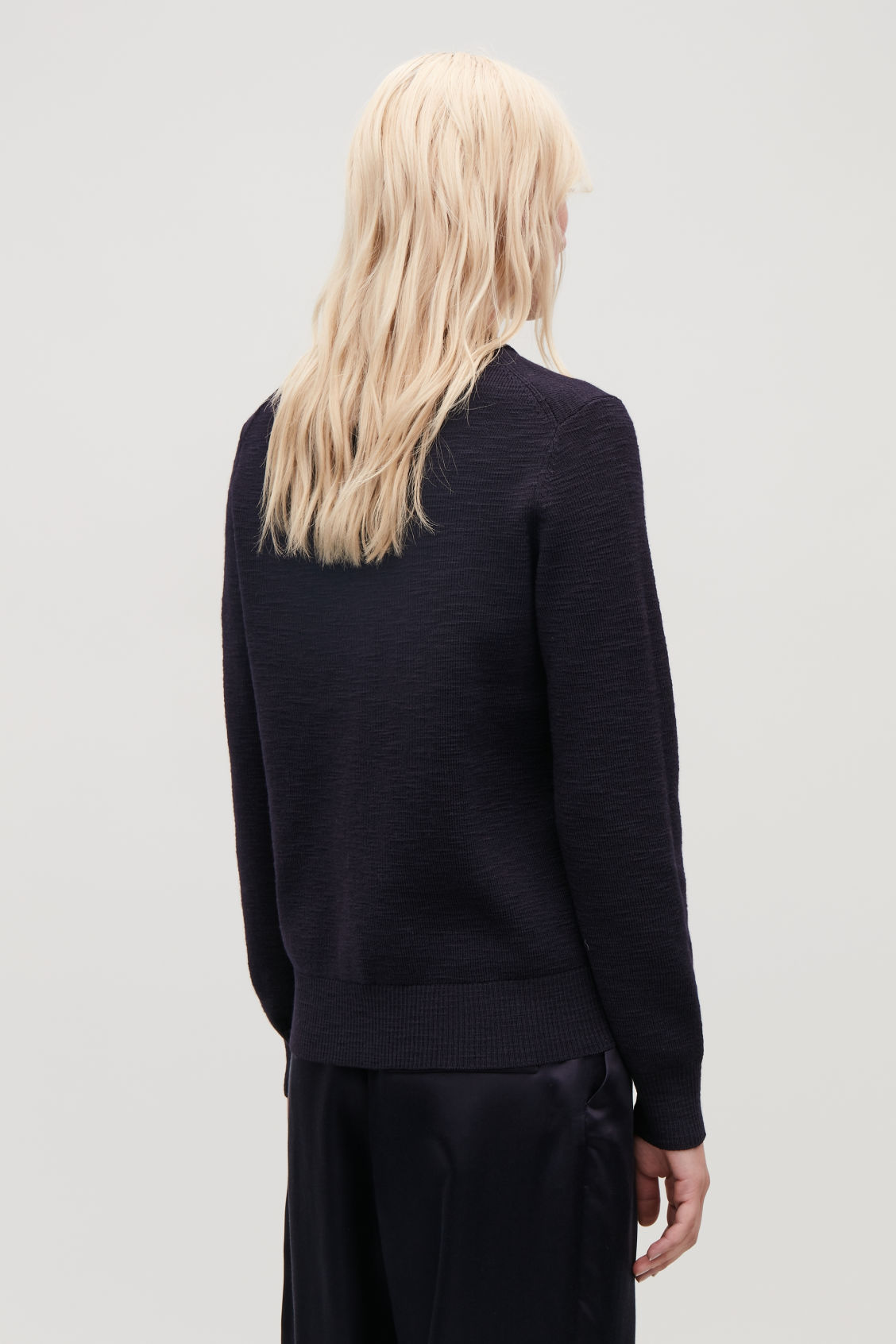 Model side image of Cos ribbed merino-wool jumper in blue
