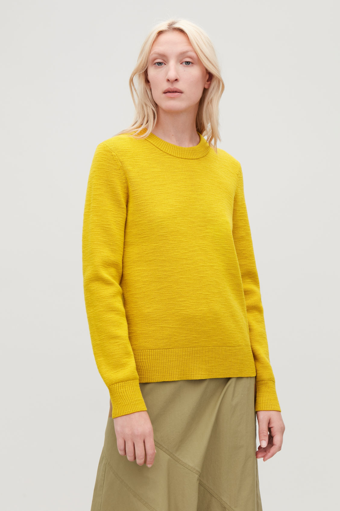 Model side image of Cos ribbed merino-wool jumper in yellow