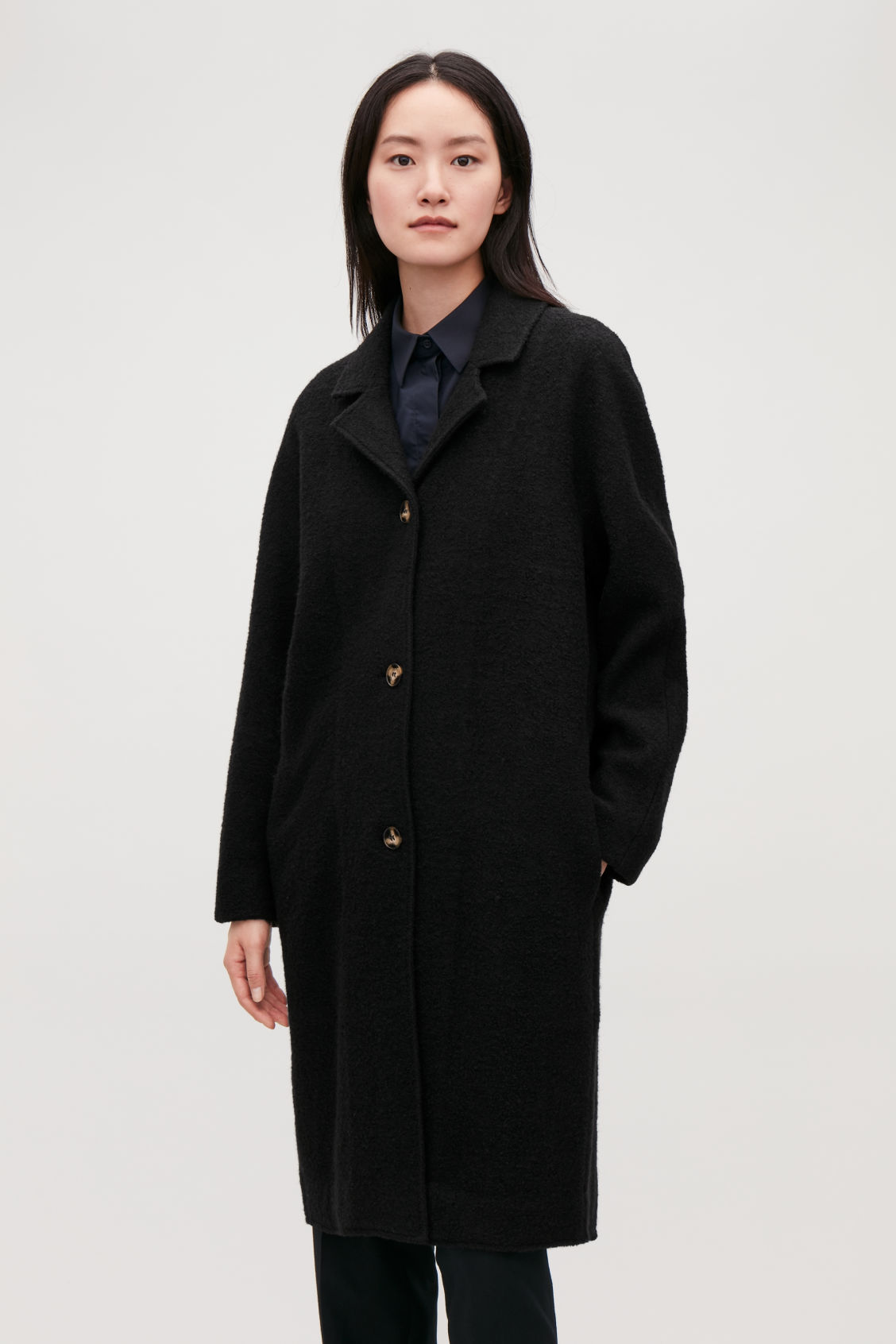 Model side image of Cos single-breasted jersey car coat in black