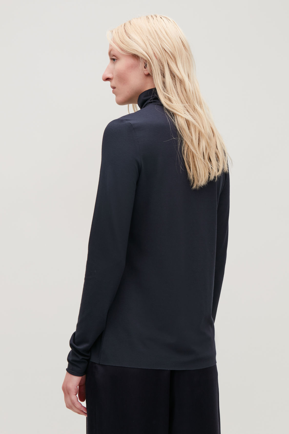 Model side image of Cos jersey roll-neck top in blue