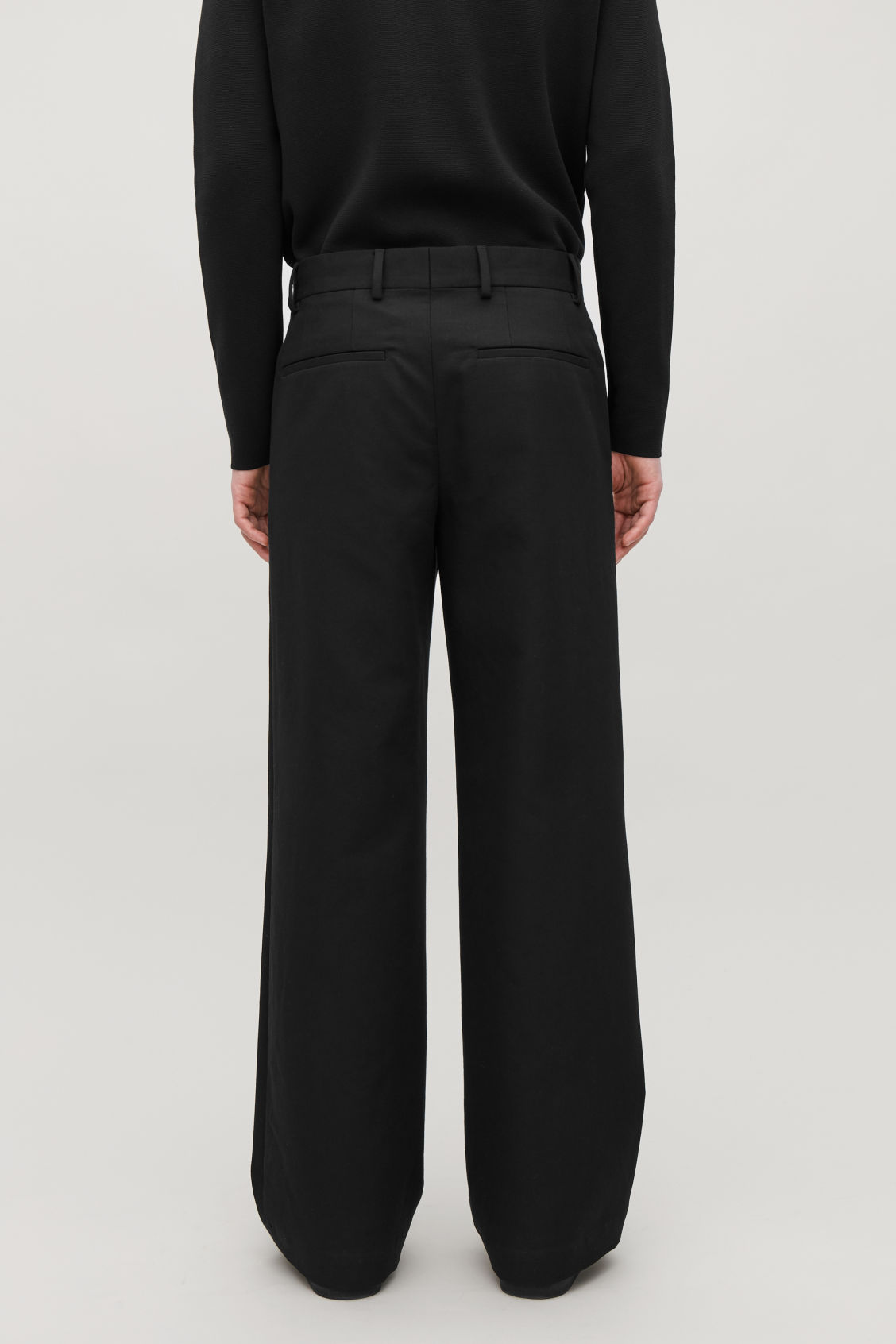 Model side image of Cos flared cotton-wool trousers in black