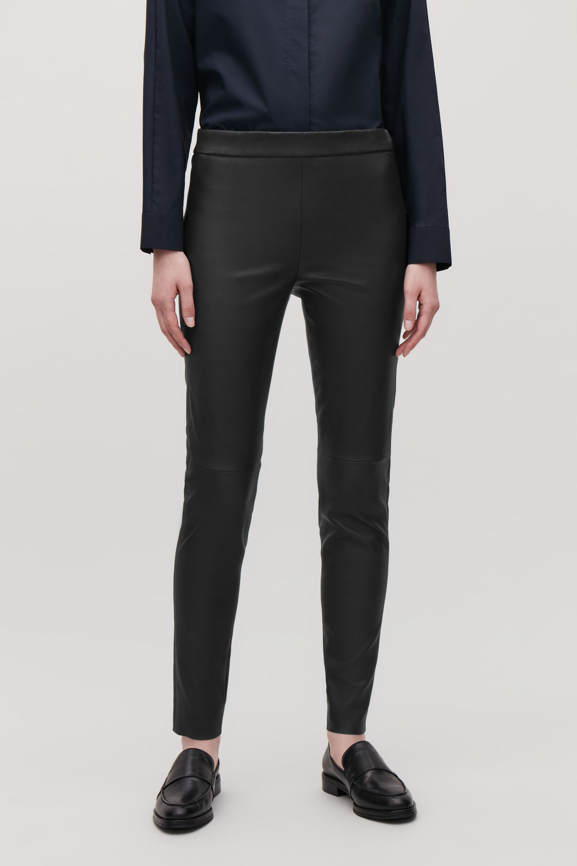 Model side image of Cos leather leggings in black
