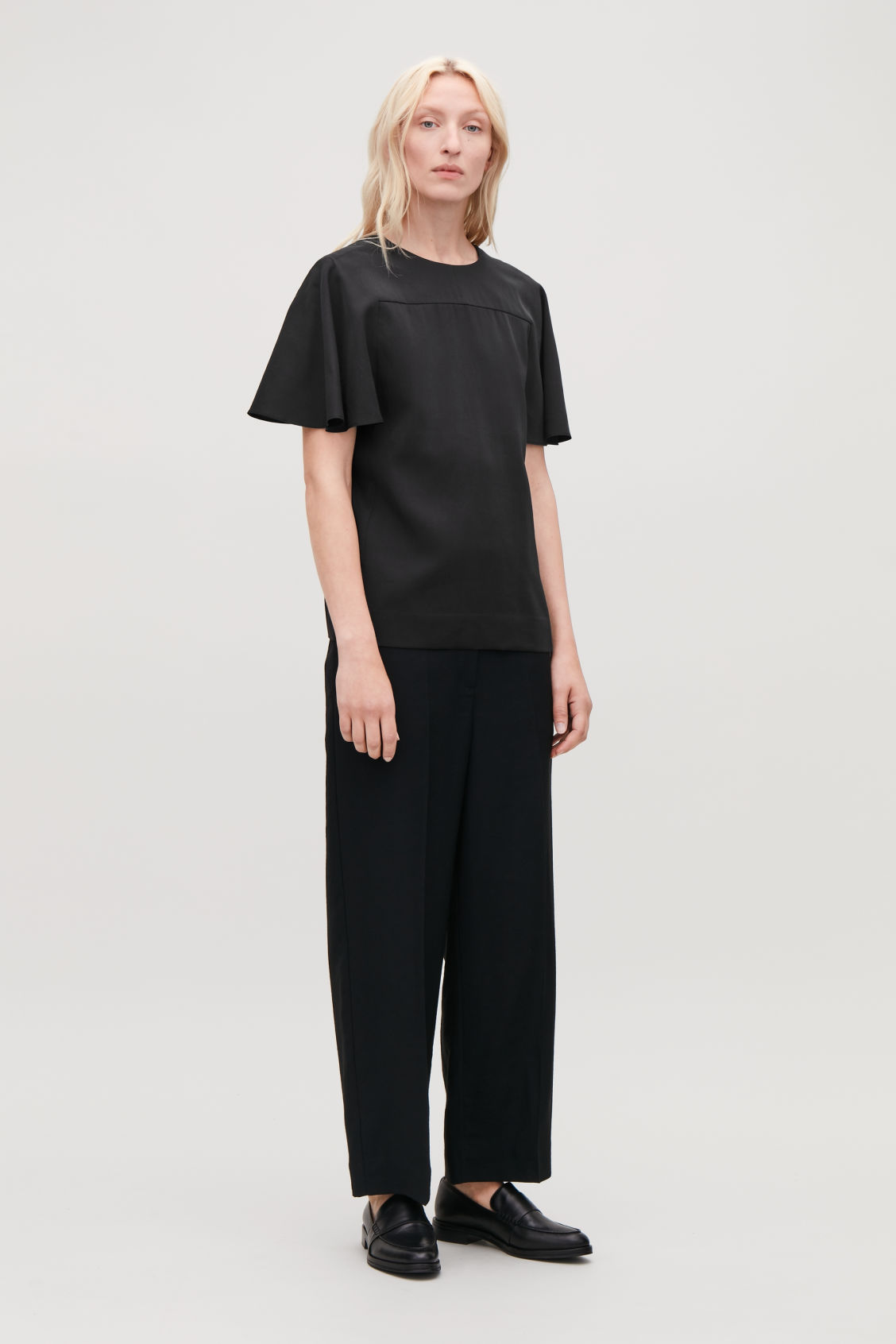 Model front image of Cos light round-neck top in black