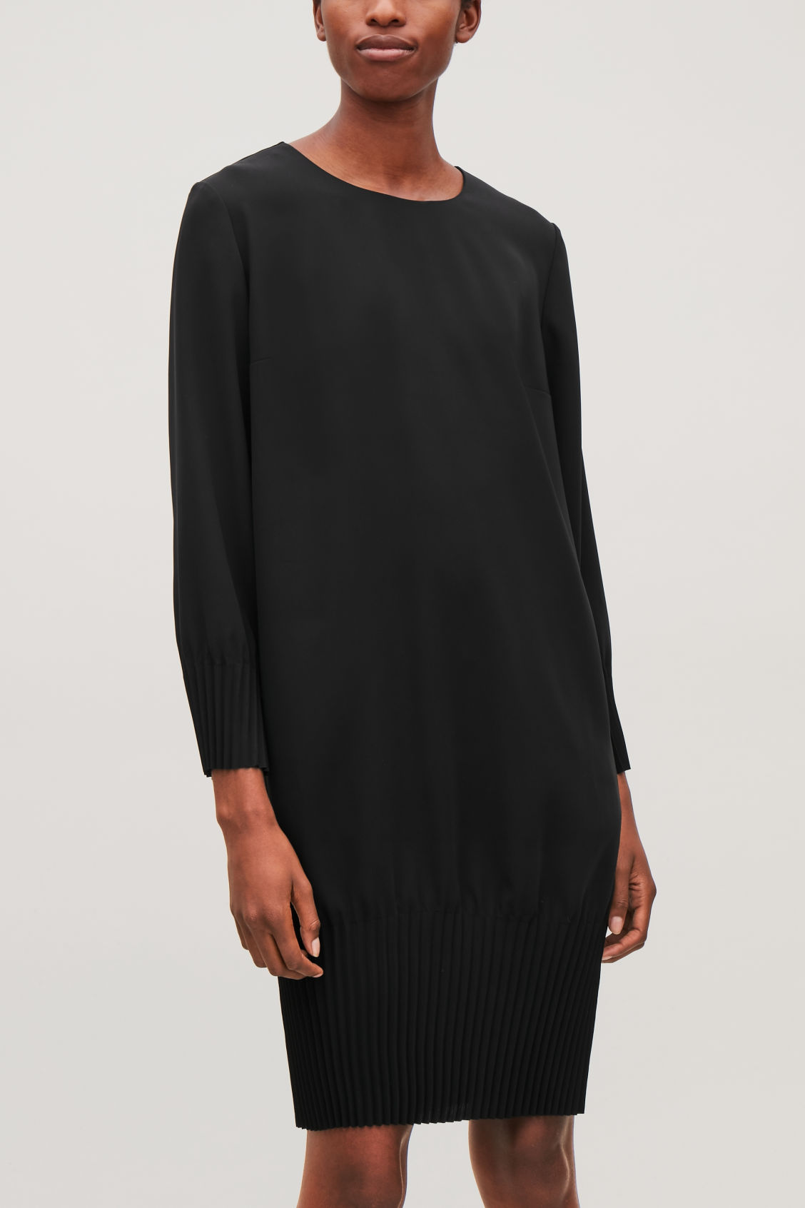 Model side image of Cos pleated dress in black