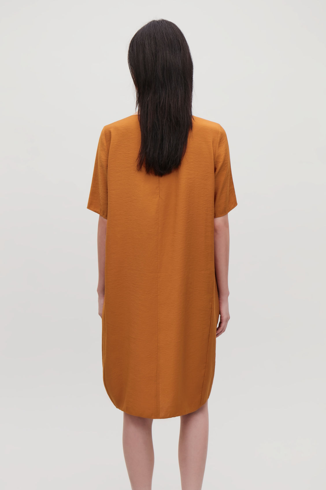 Model side image of Cos dress with gathered hem in orange